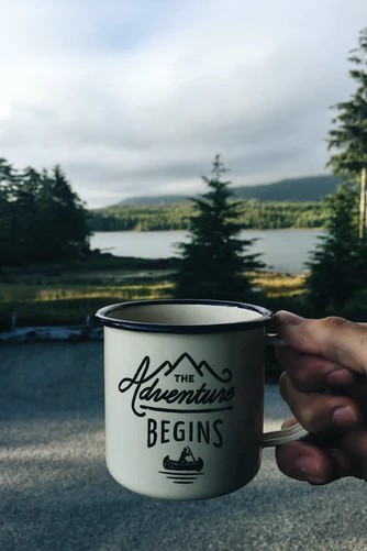 A coffee cup held displaying 'the adventure begins' in a mountain lake scene—perfect for a writer that is beginning again.