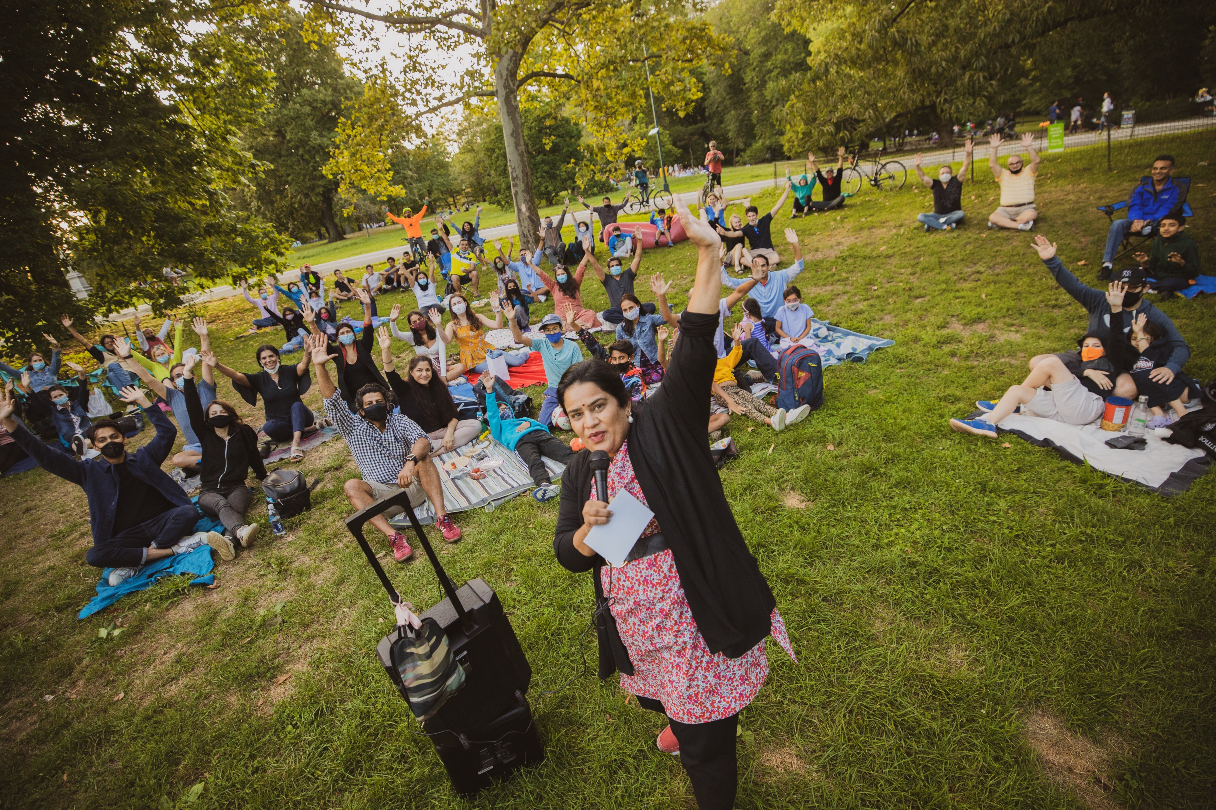 A comedian stands in front of an outdoor audience in the park, everyone cheering