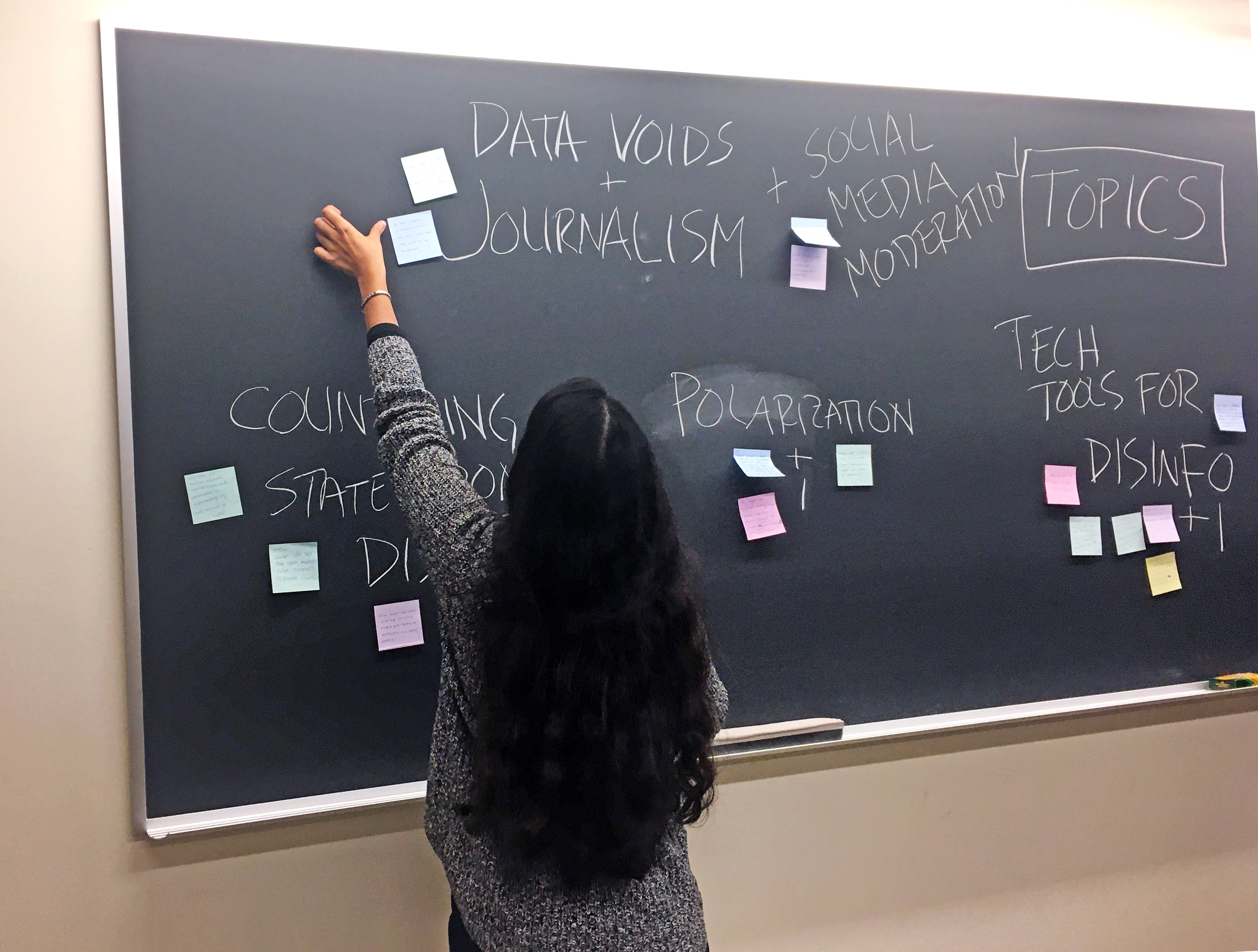 Student places sticky note on chalk board covered in key topics