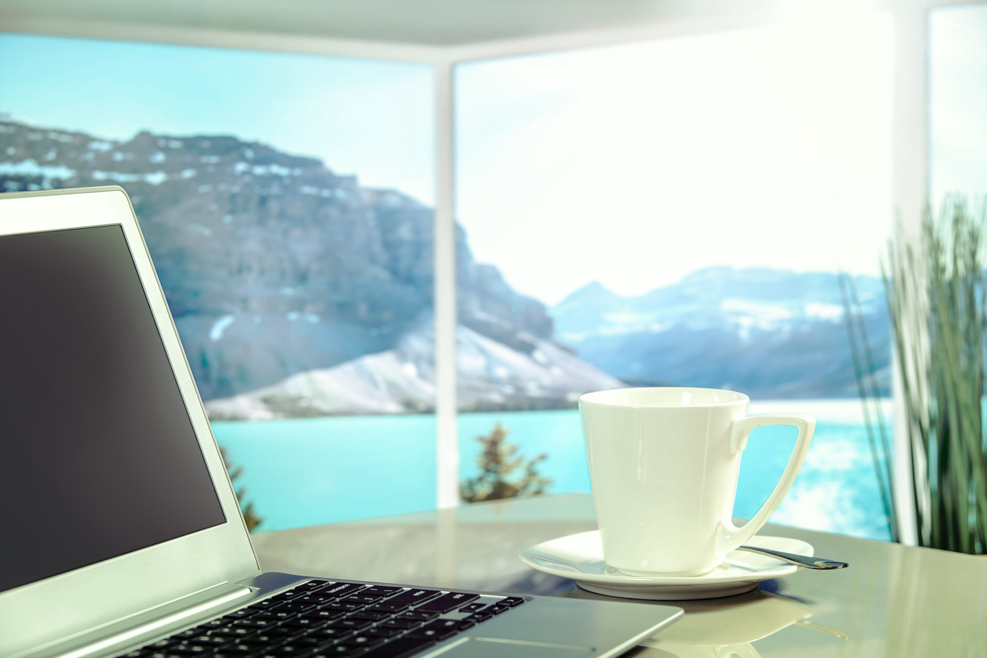 A laptop on a table overlooking a scenic getaway