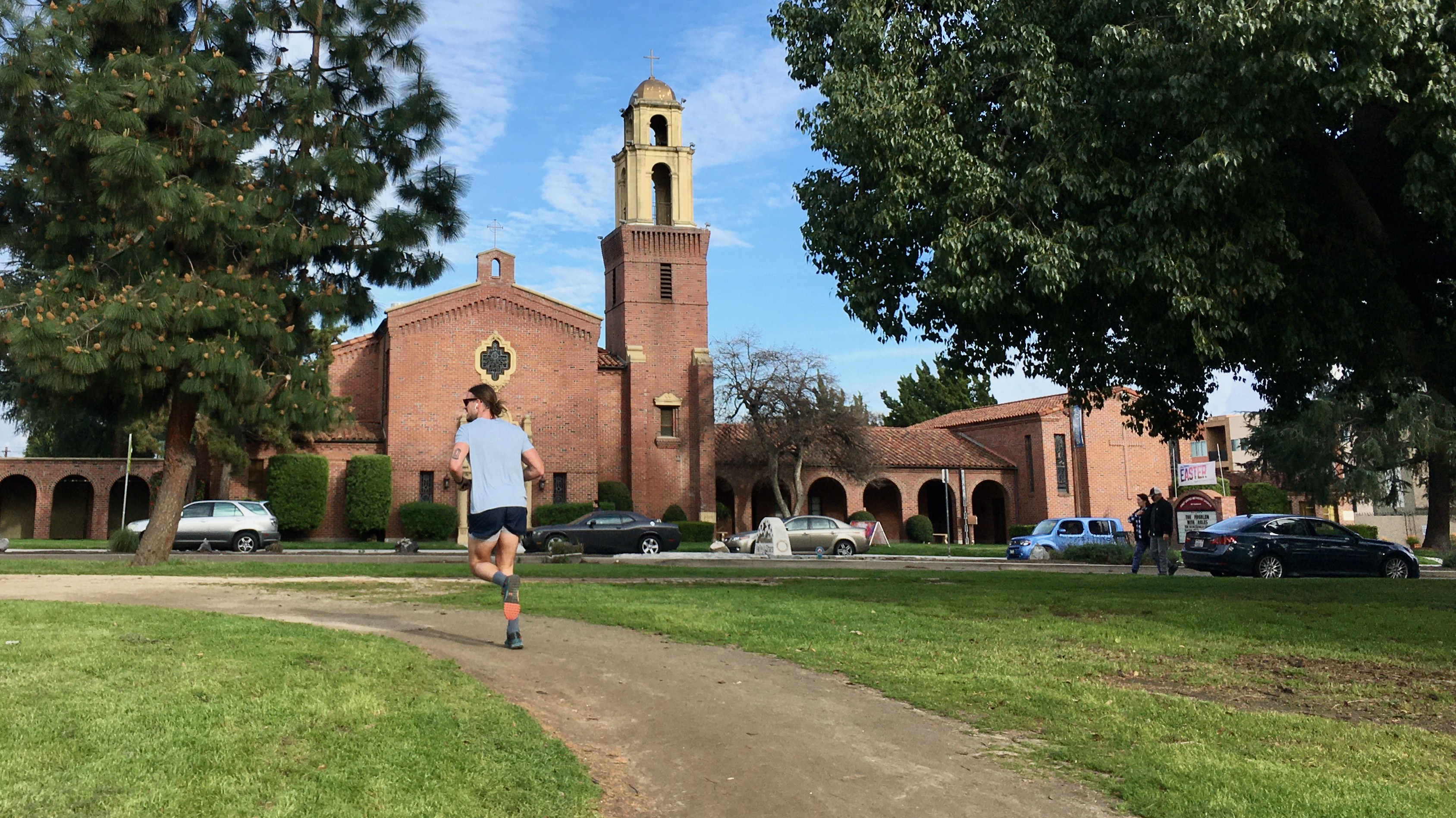 A runner turns a corner on a dirt track cutting through green lawn, in the shade of some trees