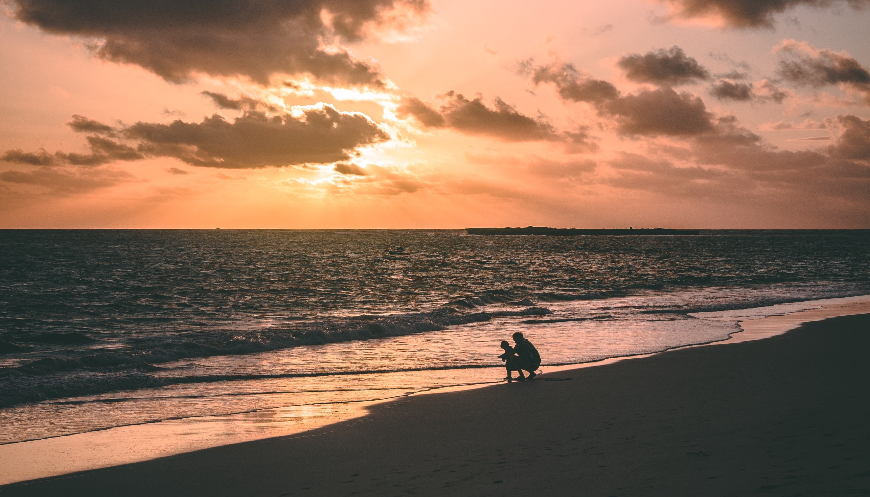 Parent and child at the edge of the ocean at sunset.