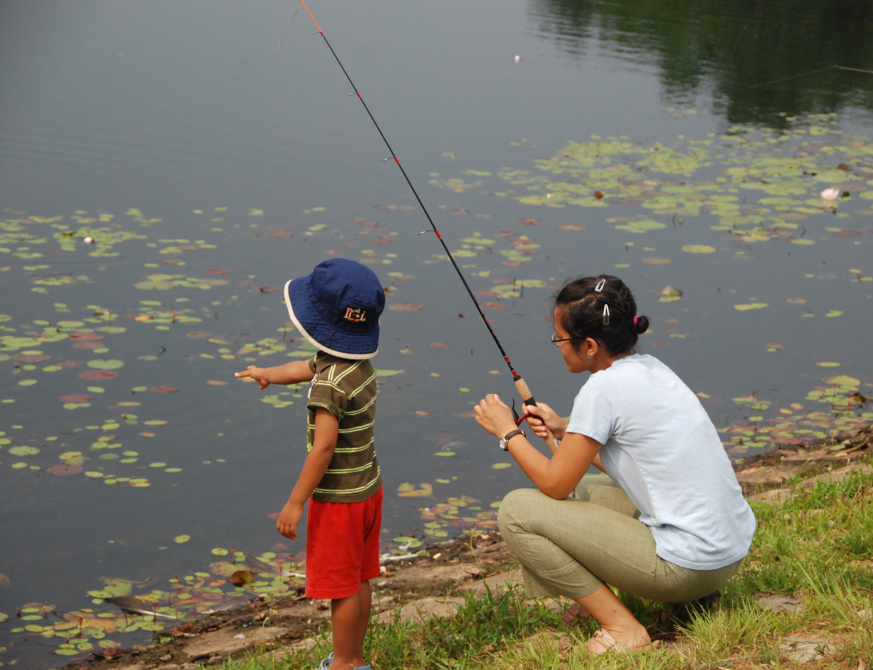 A woman fishes on the bank of a pond next to a small child.
