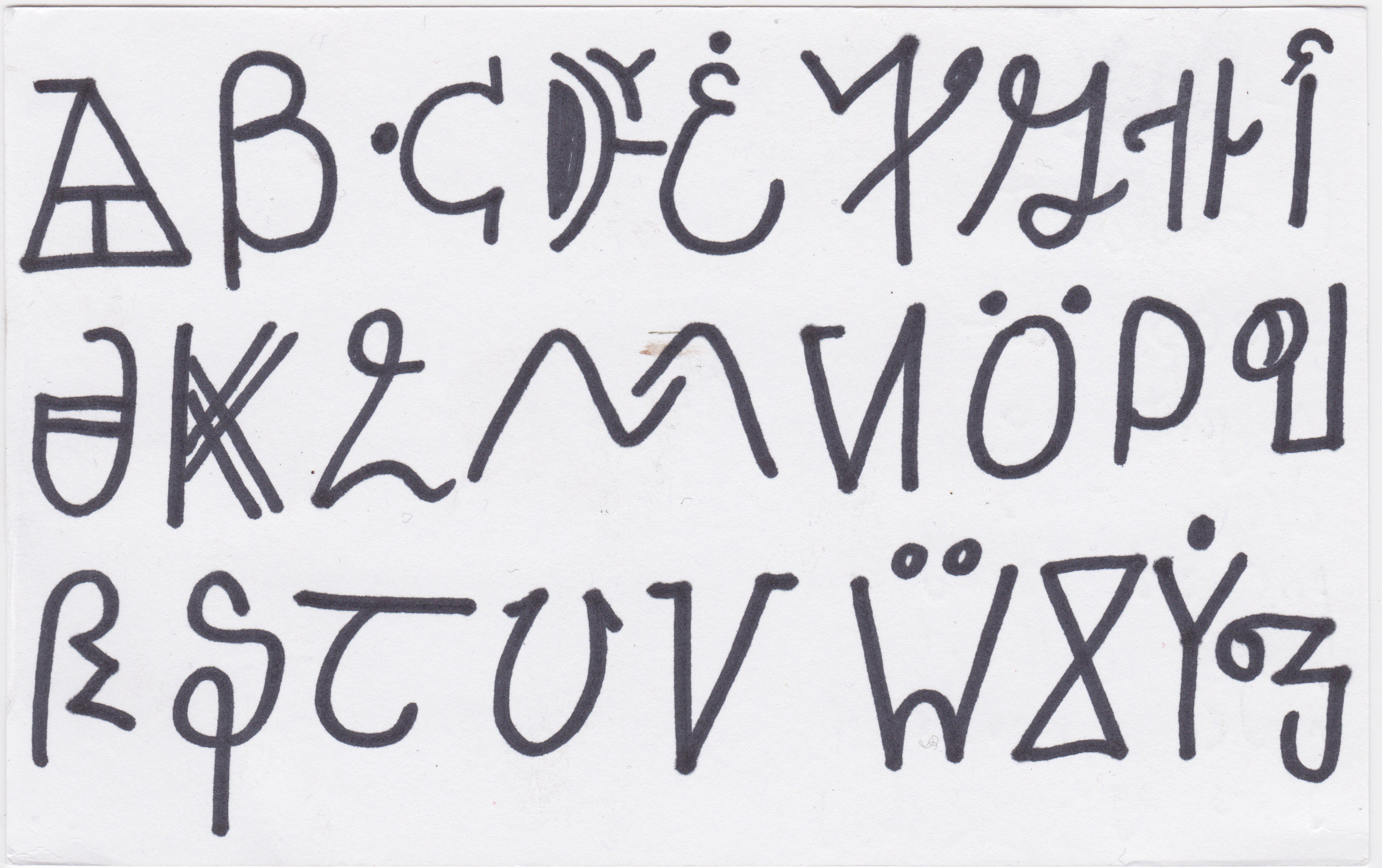 Black sharpie pen written on white thin postcard, running through the alphabet from A in the top left, to Z bottom right.