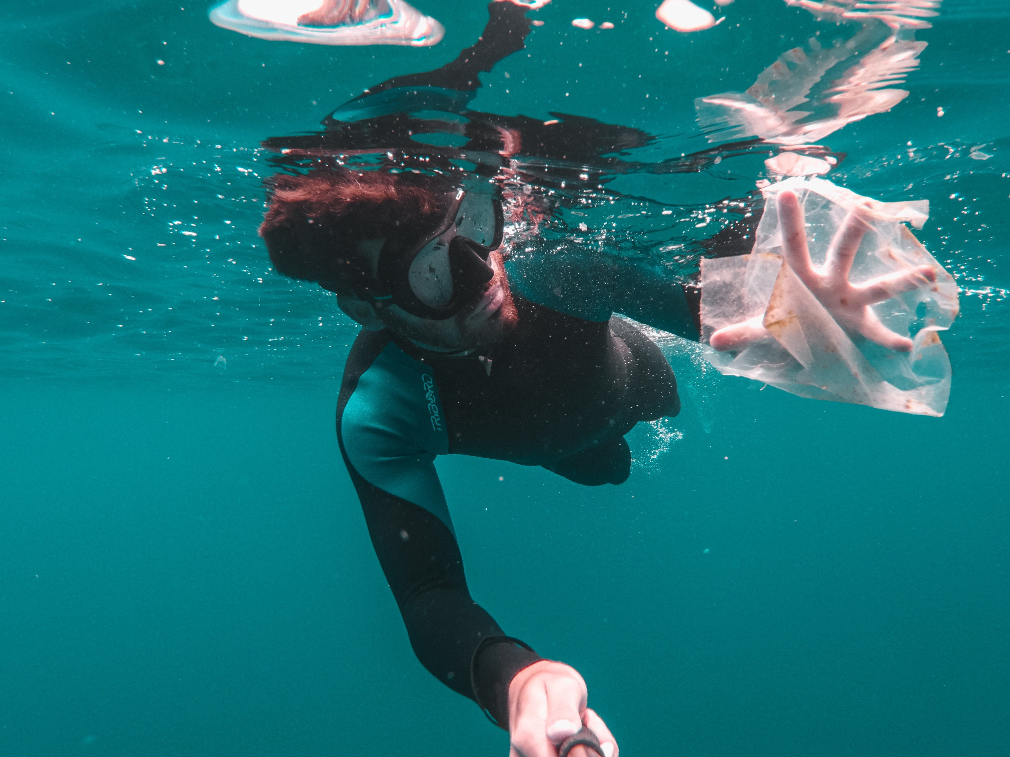 A diver in a suit and goggles, his hand reaching for plastic debris
