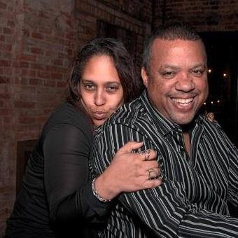 Two people embraced with the woman hugging the man in a striped shirt.
