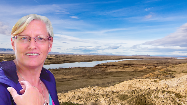 Blonde woman with glasses stands in front of a river in eastern Washington.