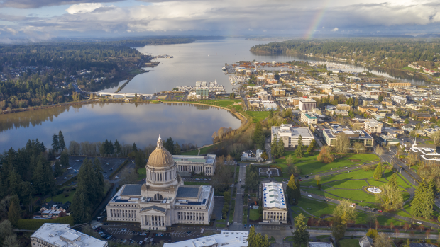 A rainbow shines over Puget Sound in Olympia, WA. The capitol building is in the foreground.