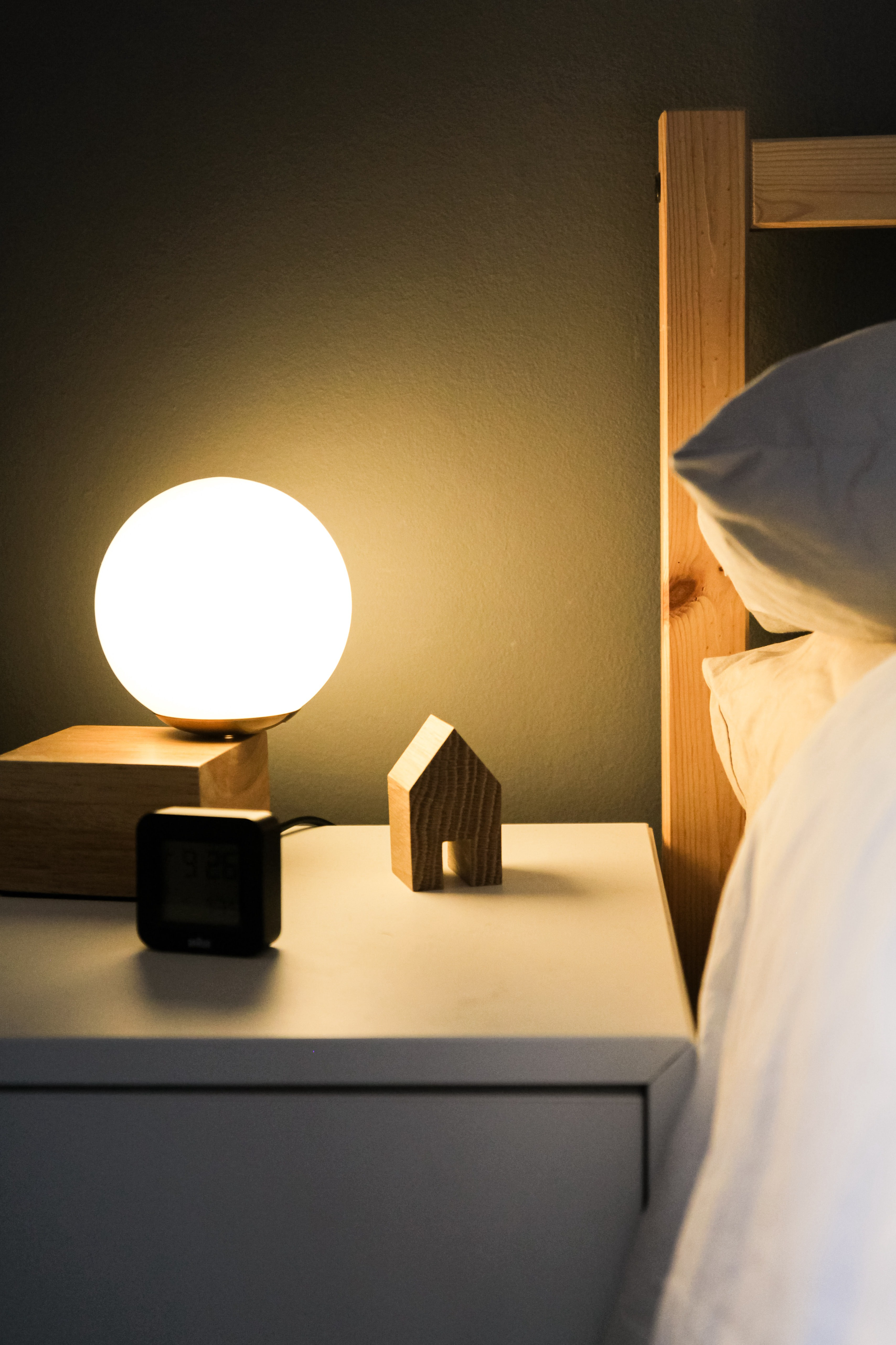 Nightstand with light, clock, and small wooden house next to a bed