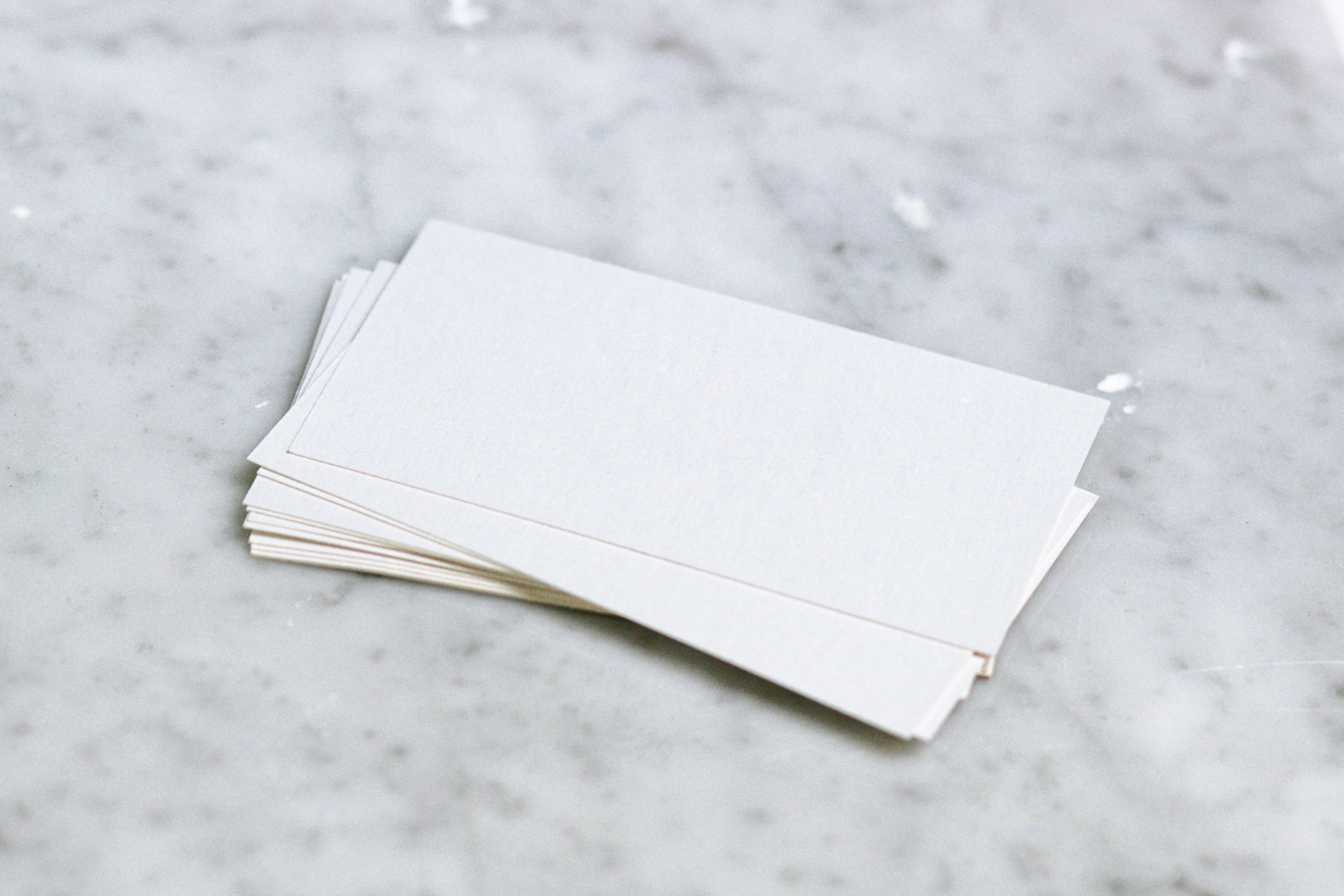 A pile of index cards on a marble countertop.