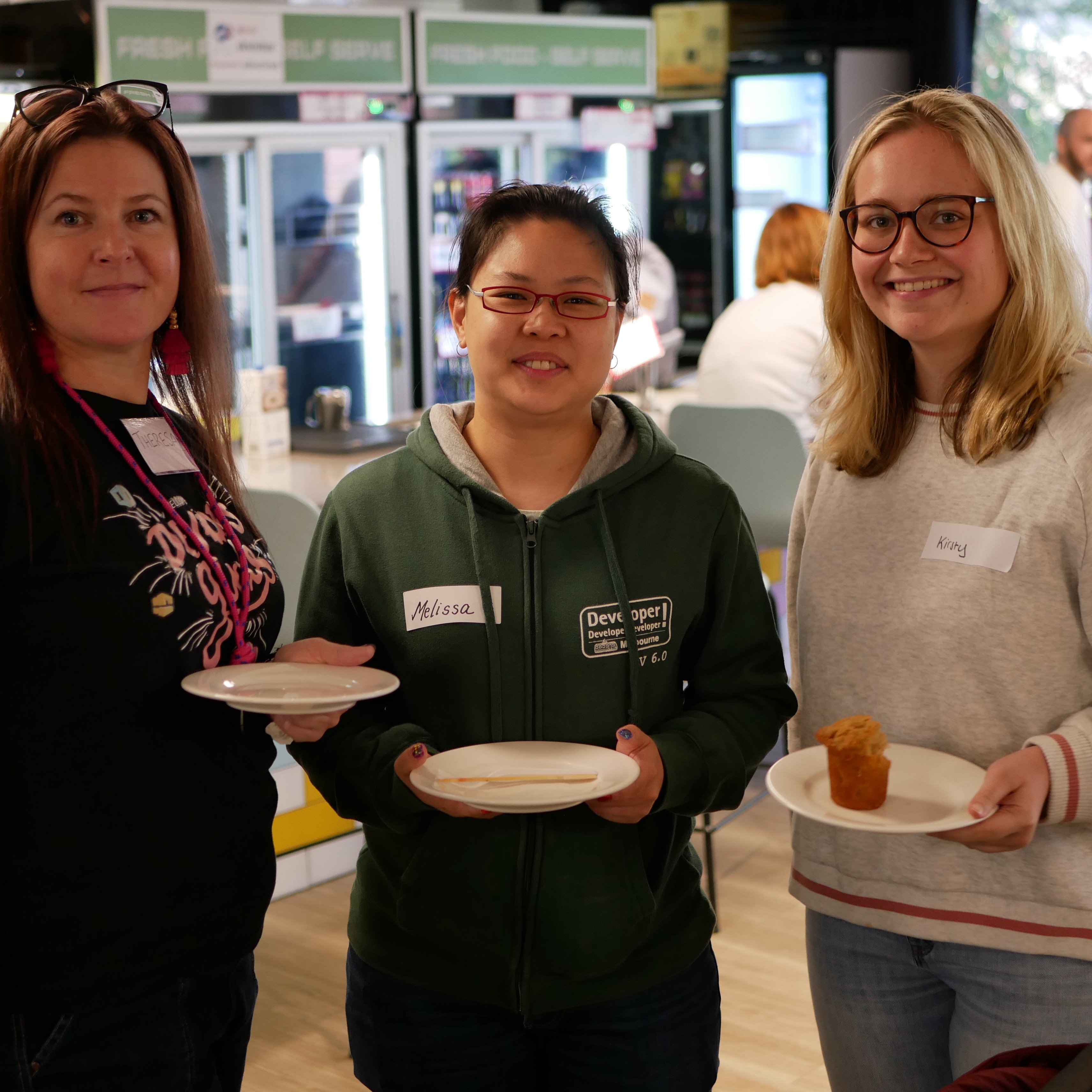 Three women are standing and holding plates with some food, smiling at the camera.