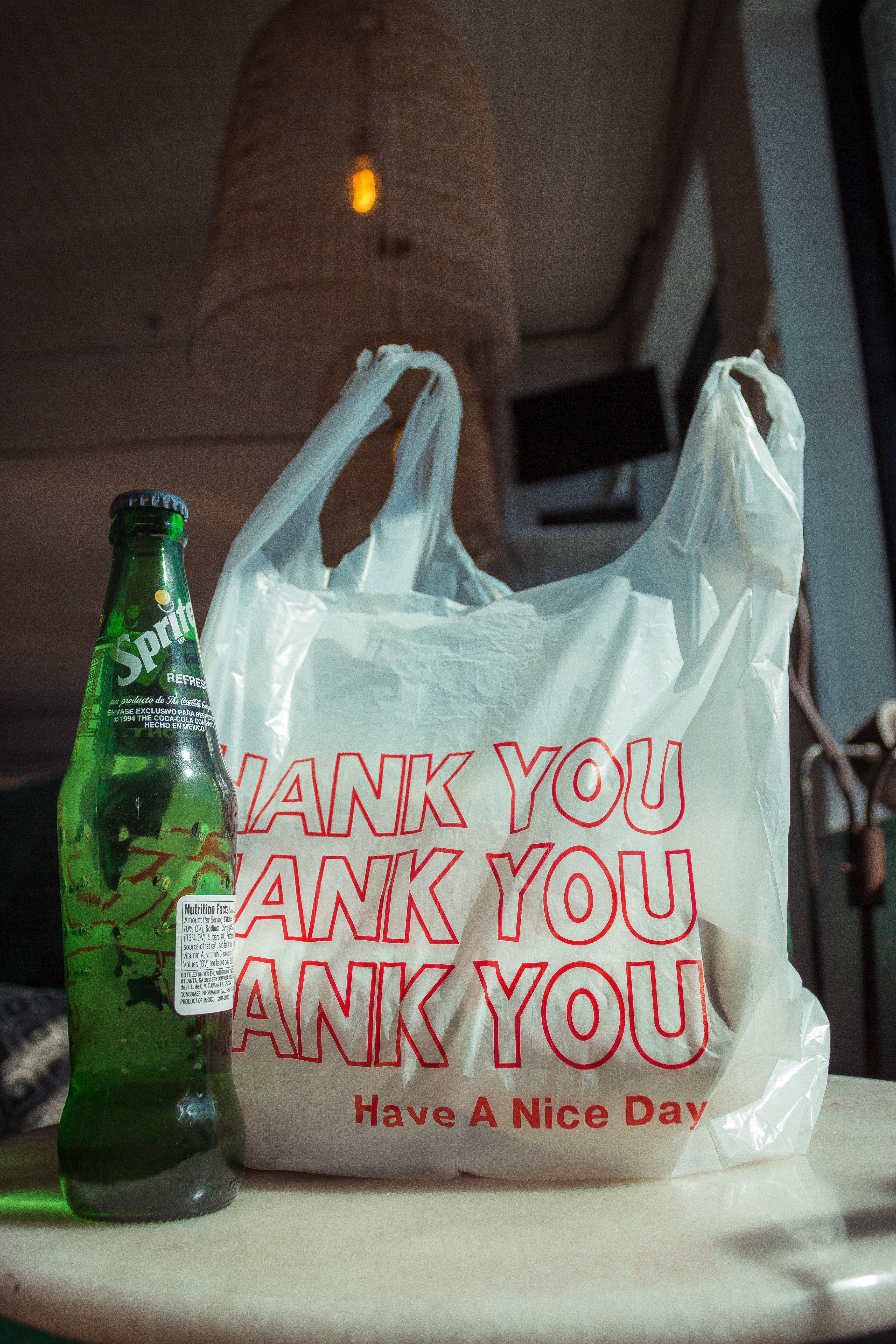 plastic trash bag and bottle of Sprite, waste created from shopping, ways to reduce waste