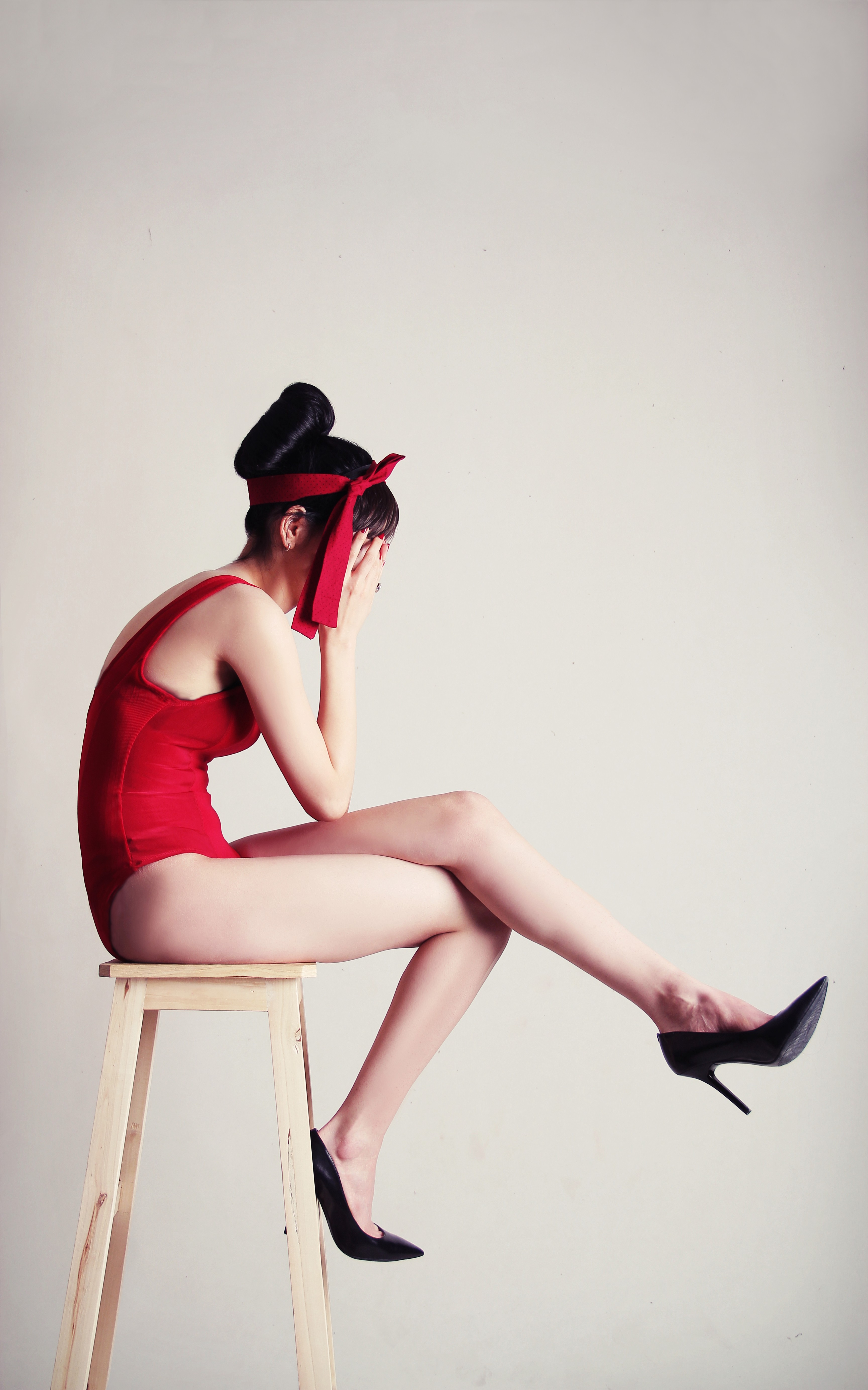 A woman in a red leotard with hands over face in despair sitting on a wooden stool.