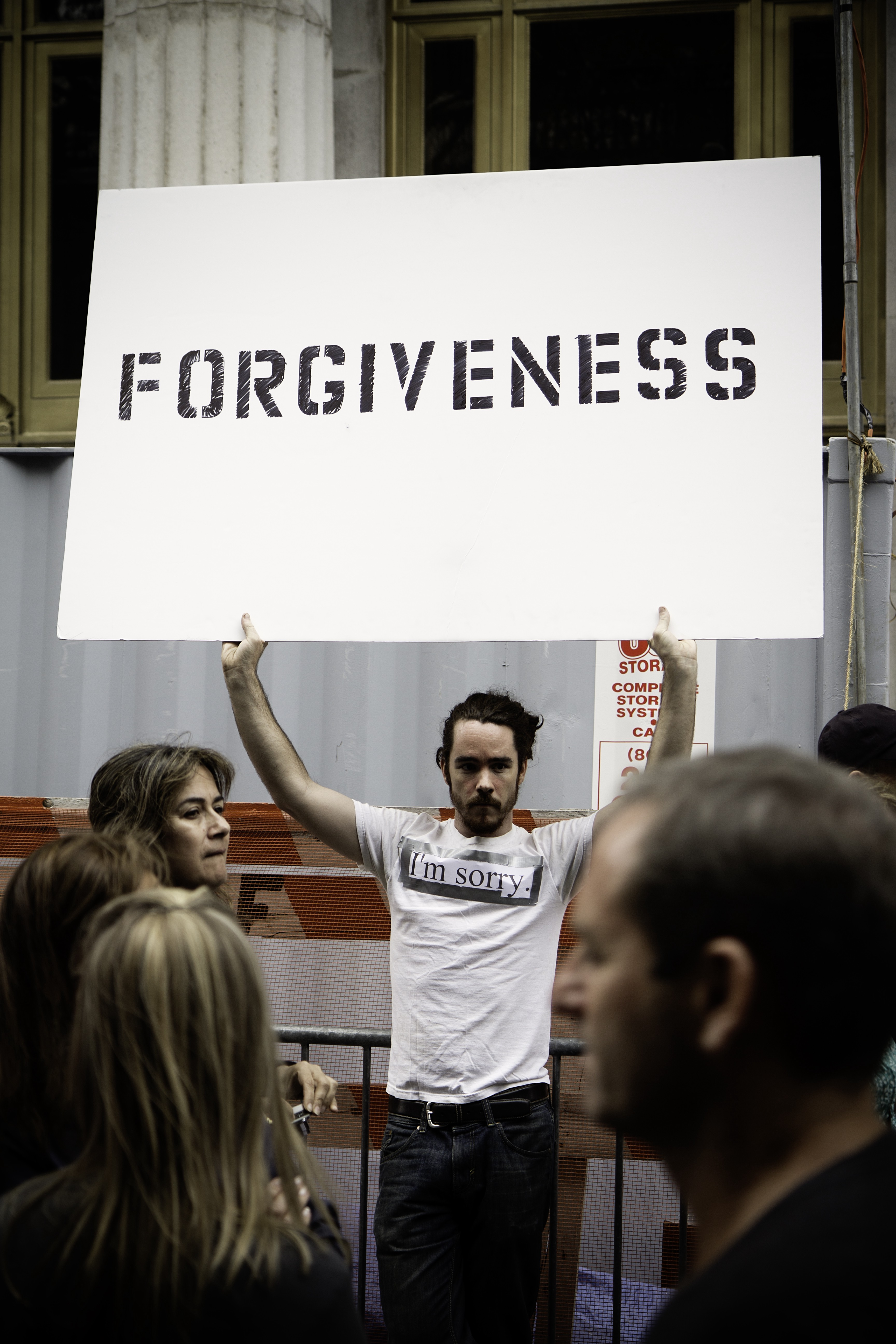 photo of man holding 'forgiveness' sign on mickey markoff air sea exec post re forgiveness.