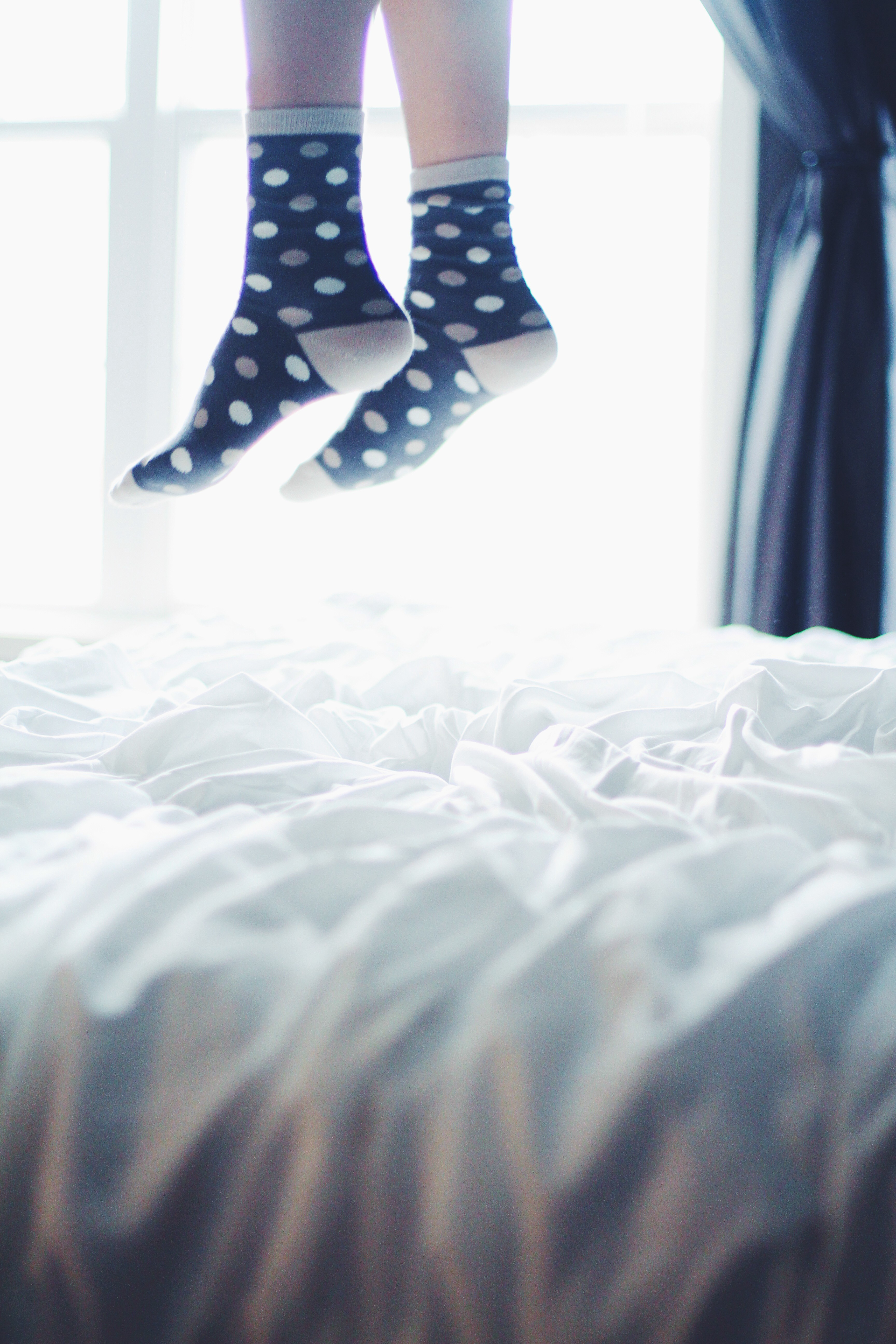 spotted socks jumping on a bed