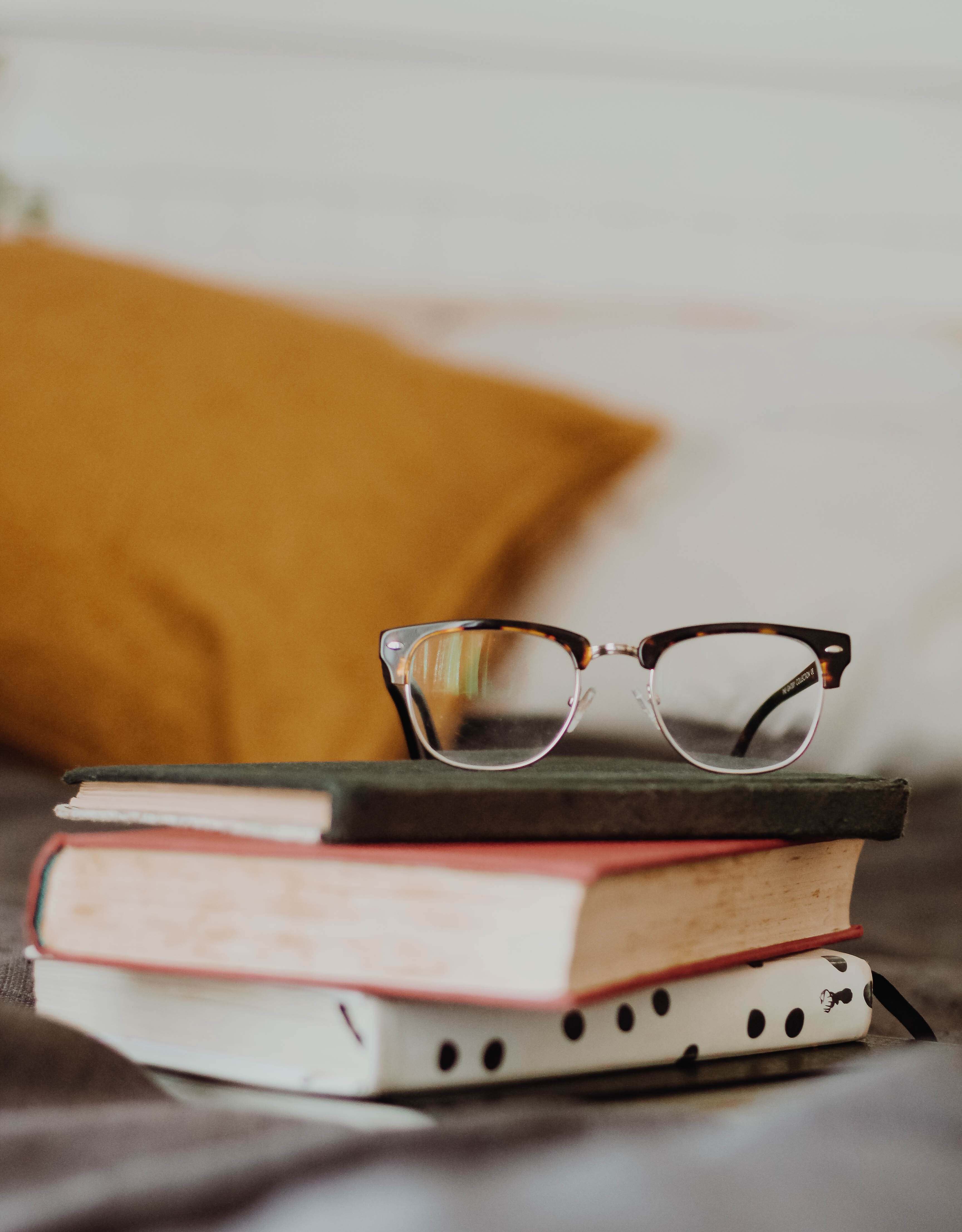 Reading glasses sitting on a stack of books.
