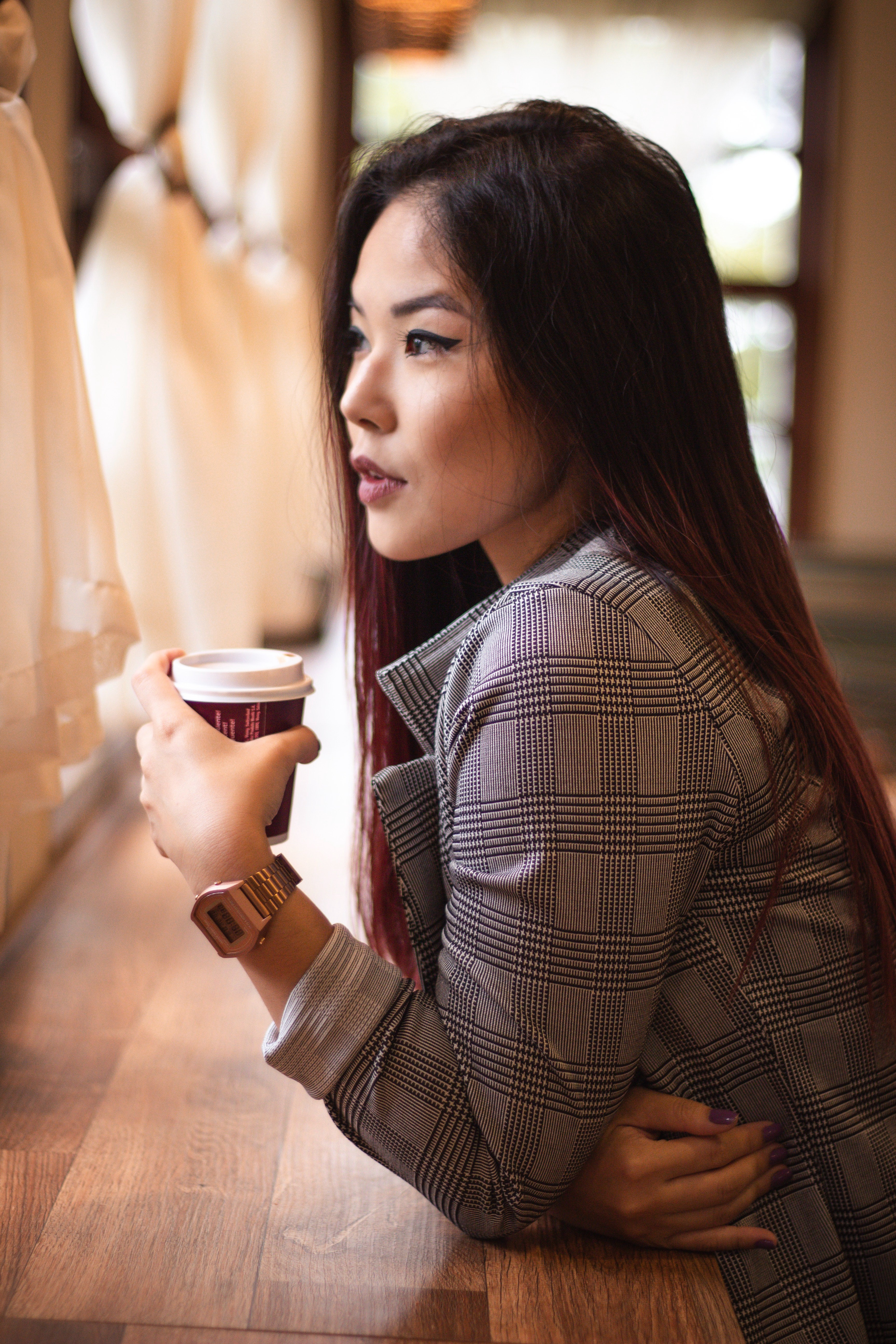 Woman looks pensively through window at cafe