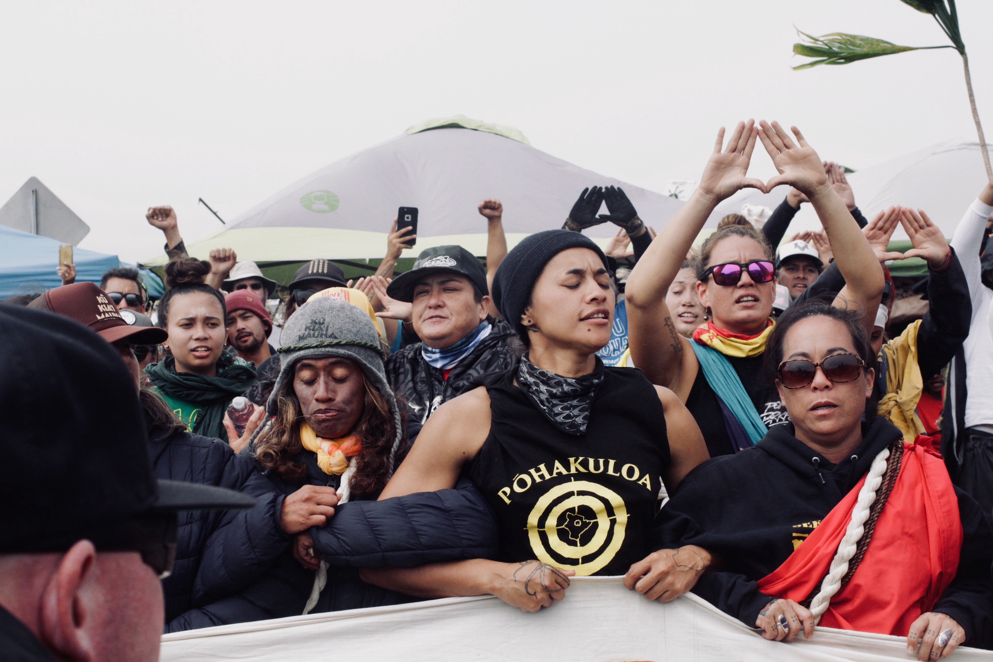 A photo of womxn and nonbinary folx creating a human barrier between the police and the kūpuna.