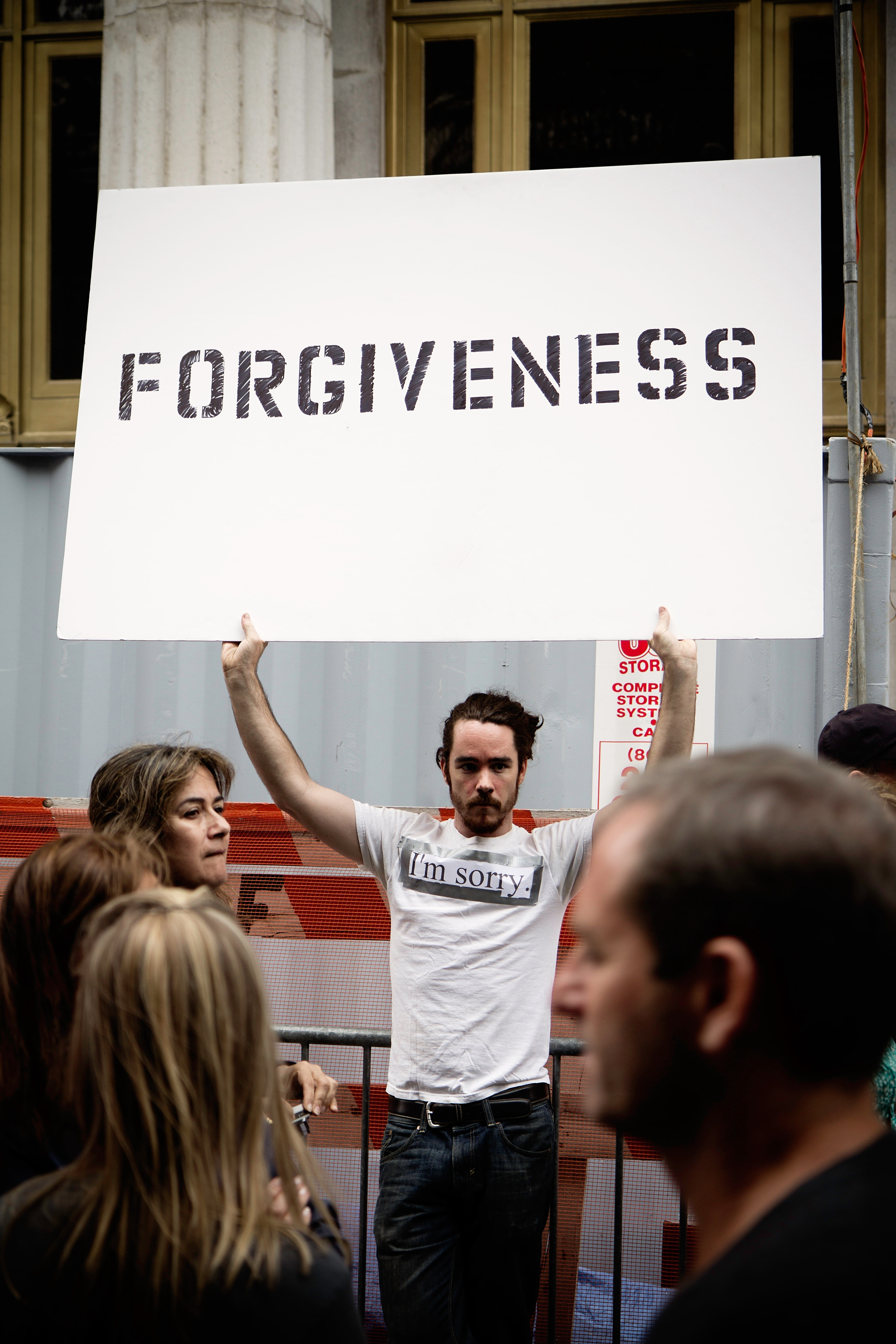 """Man holding a sign that says """"Forgiveness"""" while wearing a white shirt that says """"I'm sorry""""."""