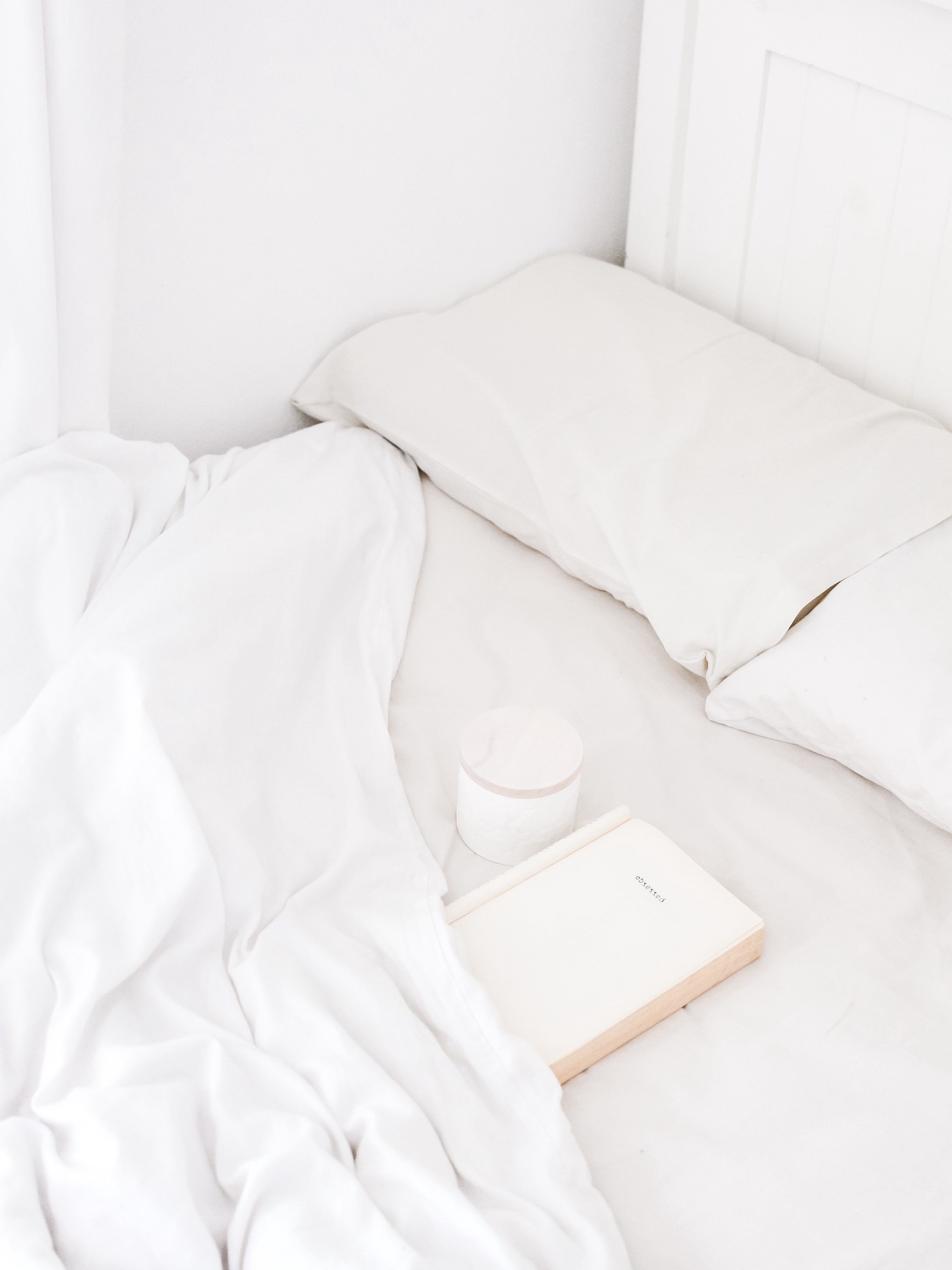 Unmade bed with book and coffee cup in covers