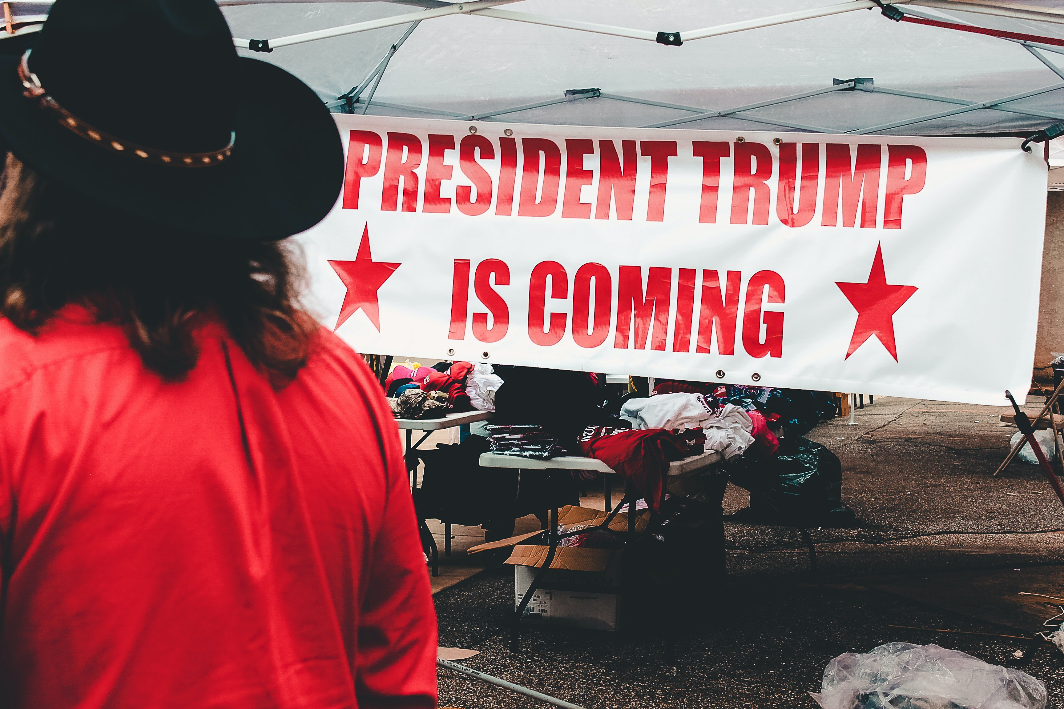 "Person in cowboy hat and red shirt walking past a tent with a big sign reading ""PRESIDENT TRUMP IS COMING"""