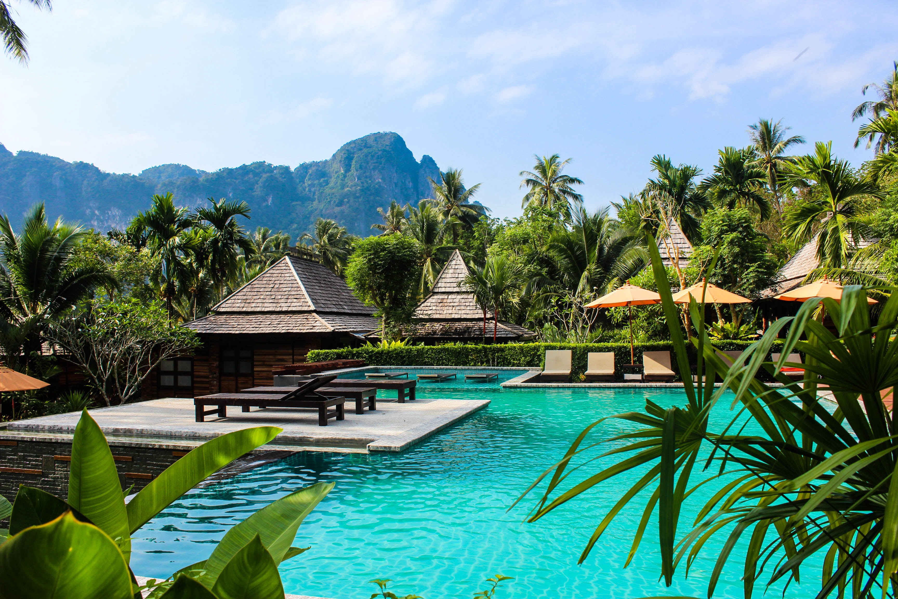 A beautiful, relaxing hotel scene in a lush jungle. Bungalows sit over turquoise water with mountain peaks in the distance.