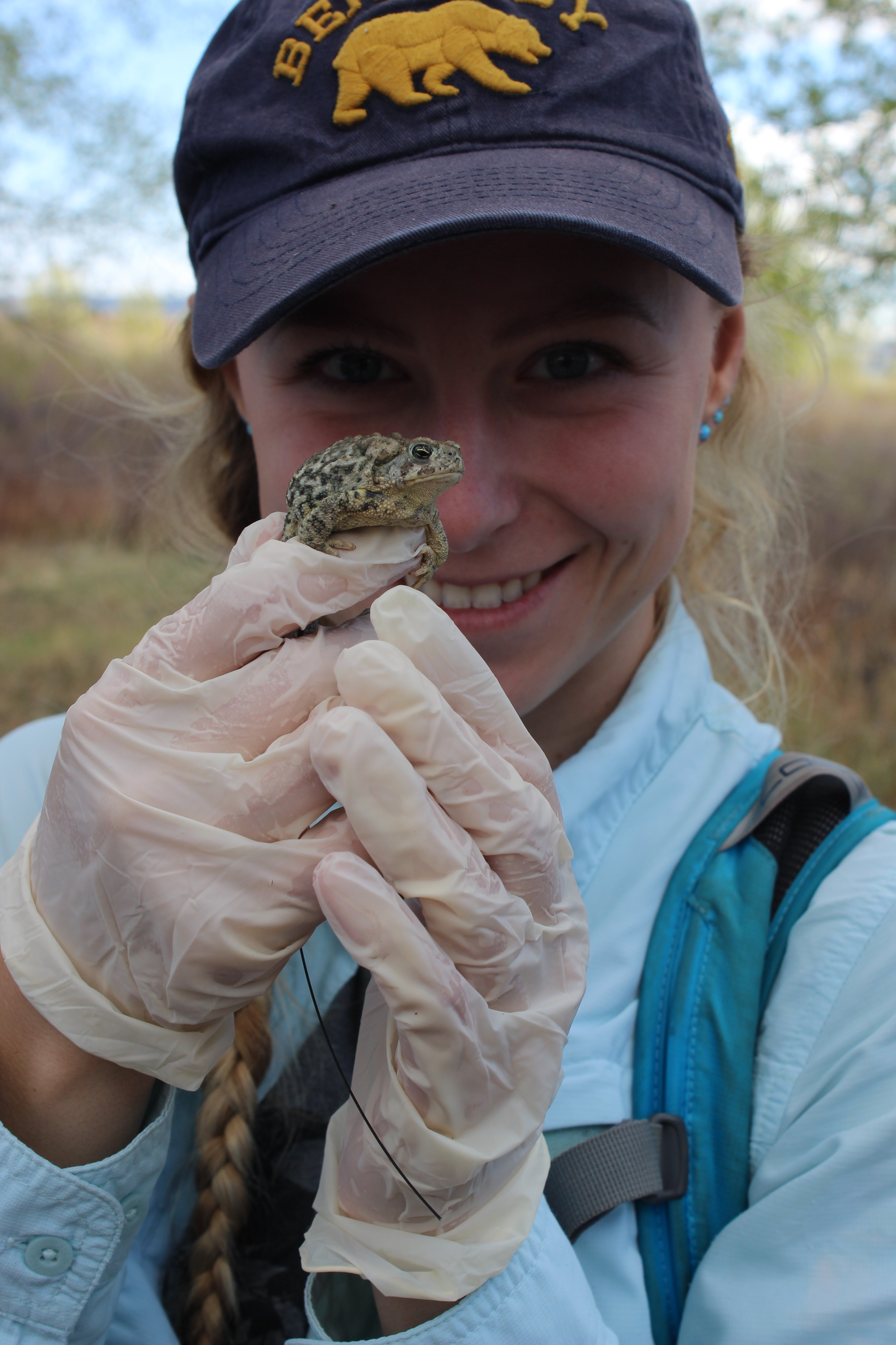 girl with ball cap and long blonde braid holding a Wyoming toad in front of her face and smiling