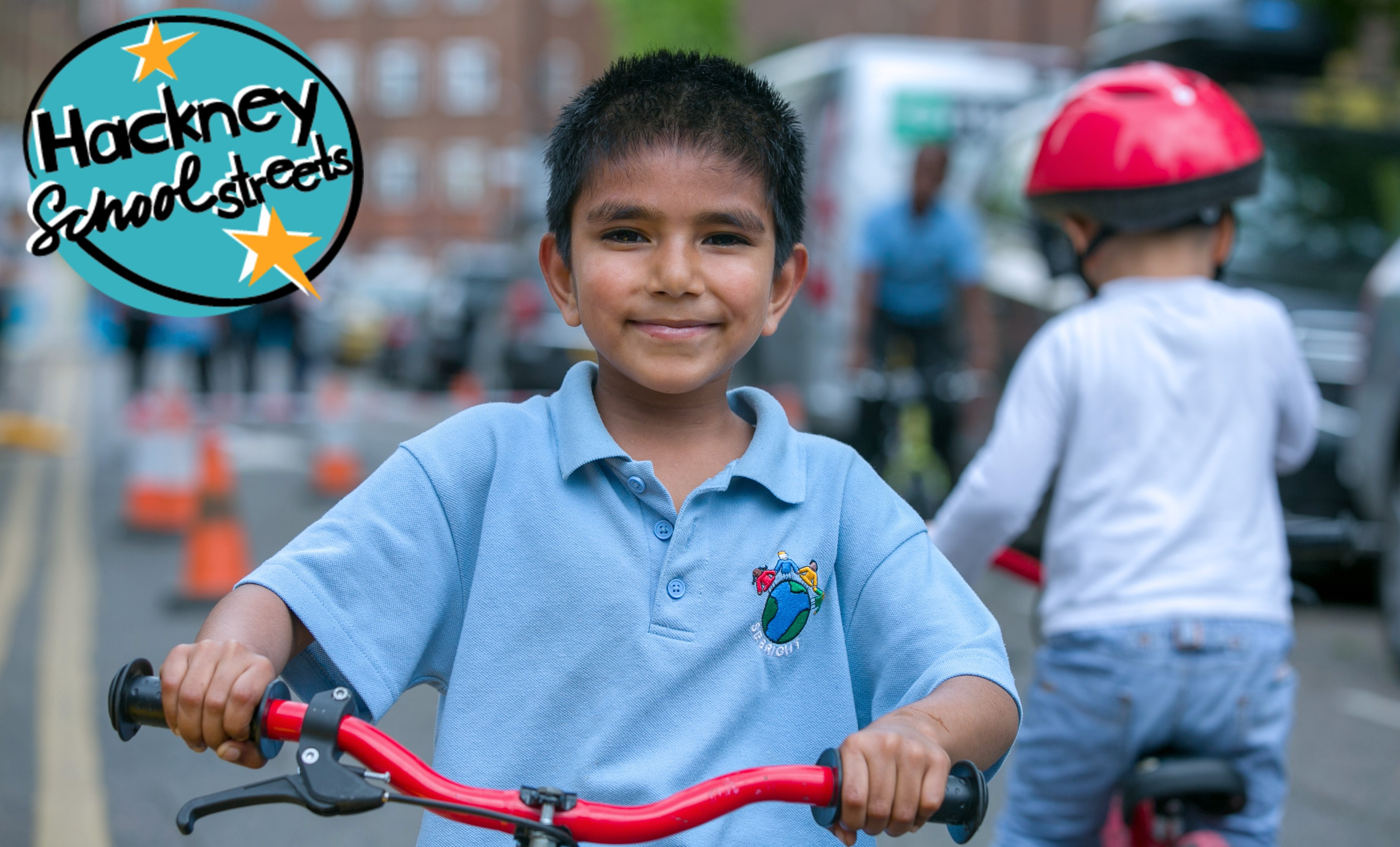 """A child on bike smiles into the camera. The aqua-and-yellow """"Hackney School Streets"""" logo is in the corner."""