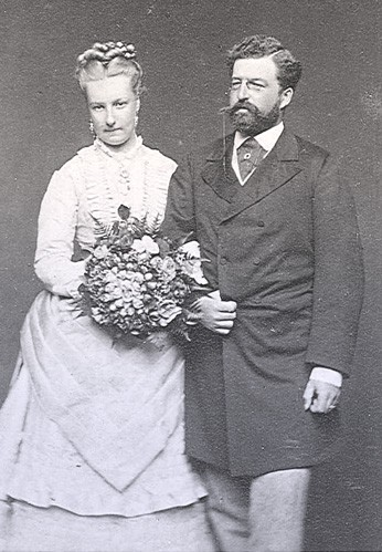 Louise and Philip standing together. Their arms are linked and she's holding a bouquet of flowers.