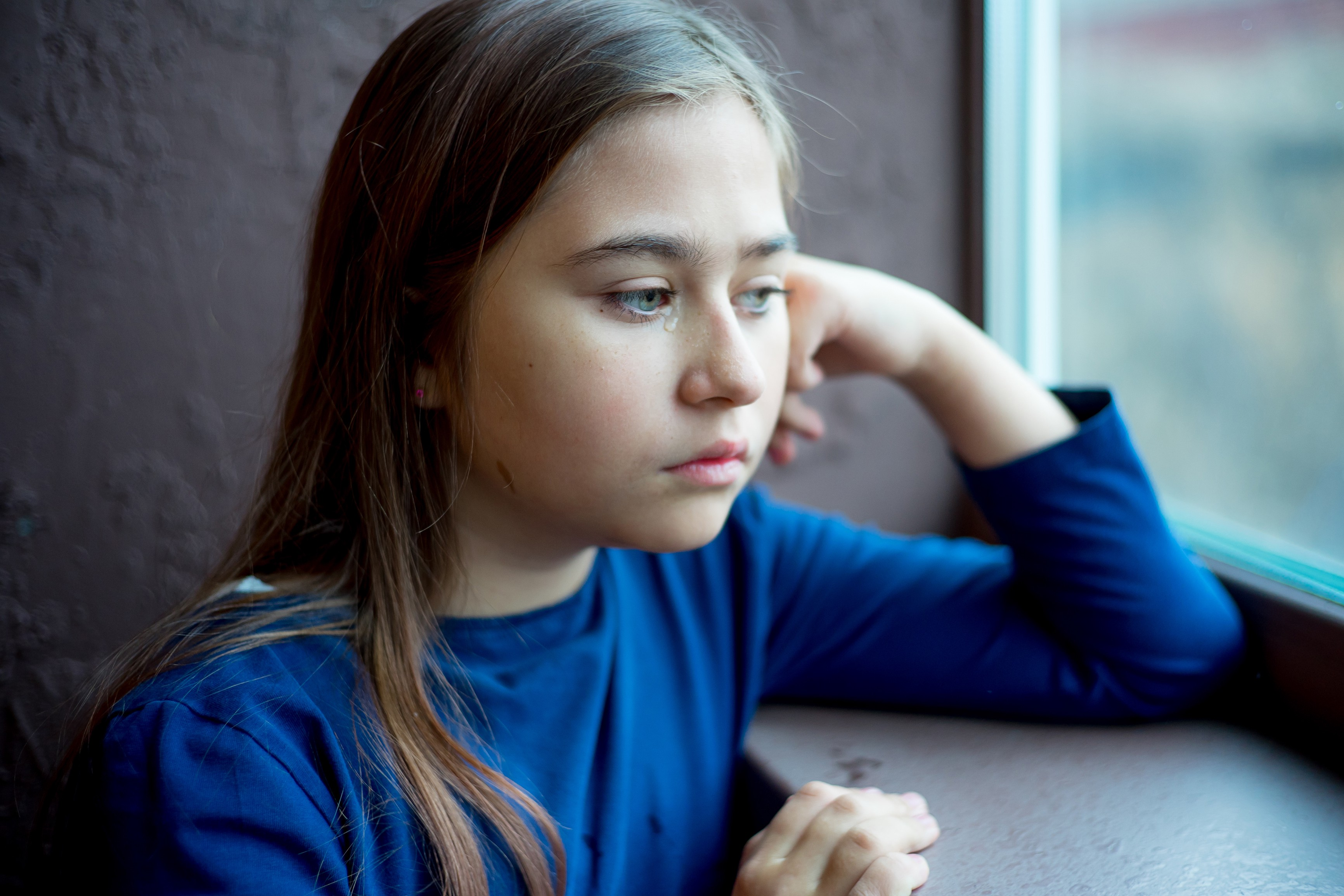Little girl sad and alone staring out of window
