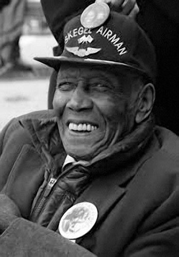 Image of graphic designer Eugene Winslow. He is an elderly African American male, smiling in a black and white photograph wearing a zipped up winter coat and hat with white text on it.