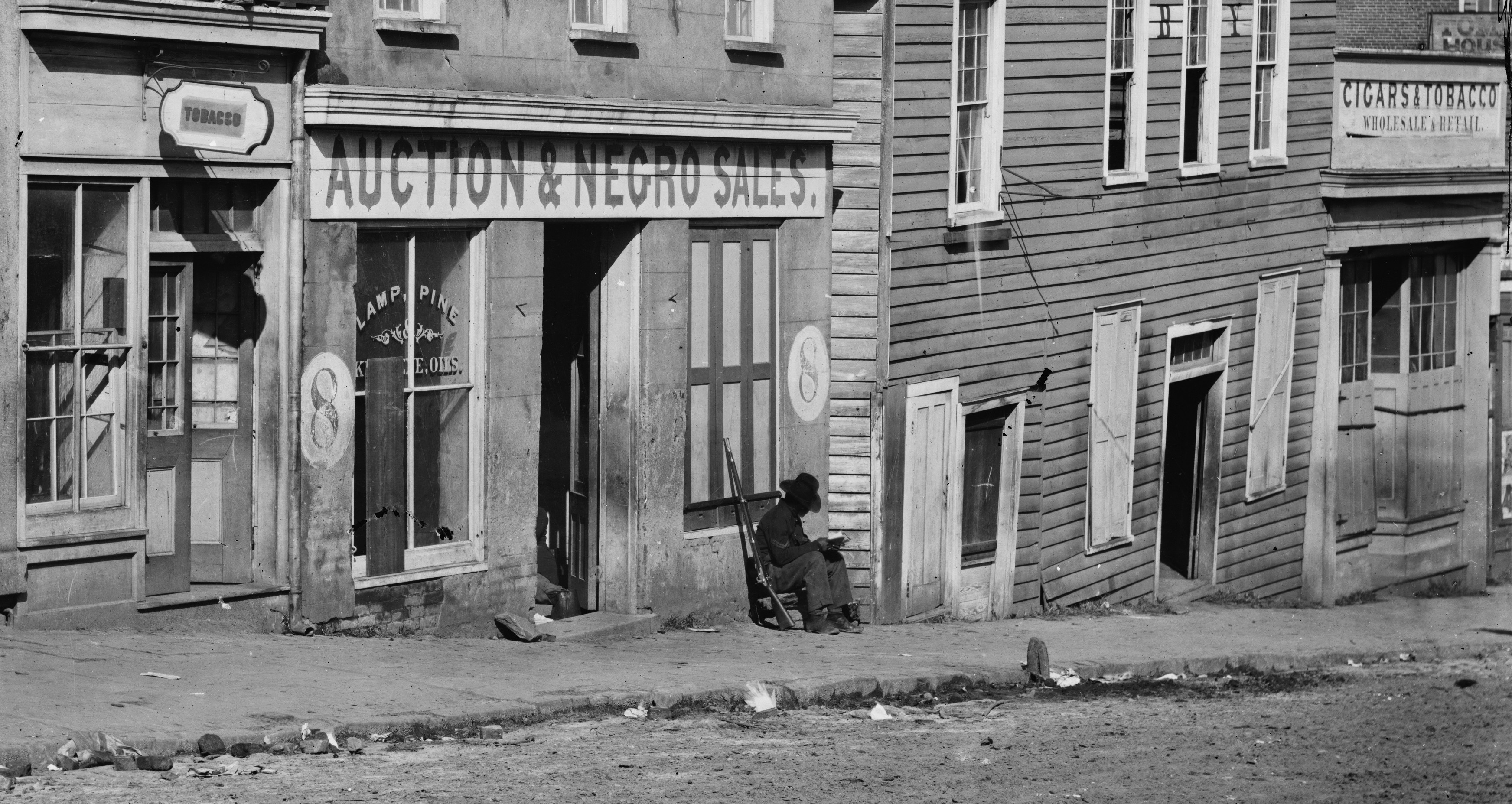 """Old storefronts in Atlanta circa 1864 including one with a sign that reads """"Auction & Negro Sales."""""""