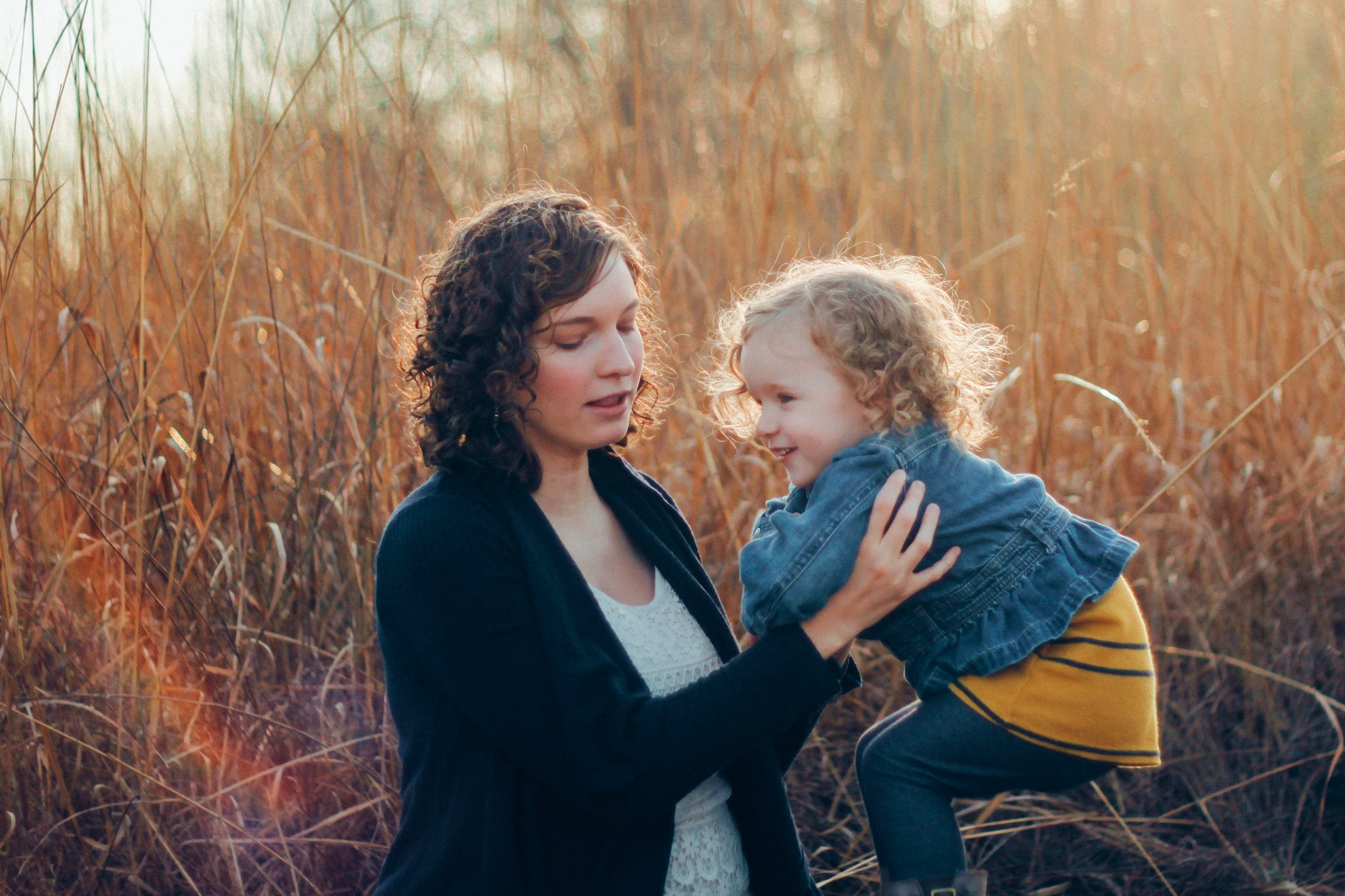 Adult with brown curly hair lifts a smiling toddler with blonde curly hair, in a wheat field