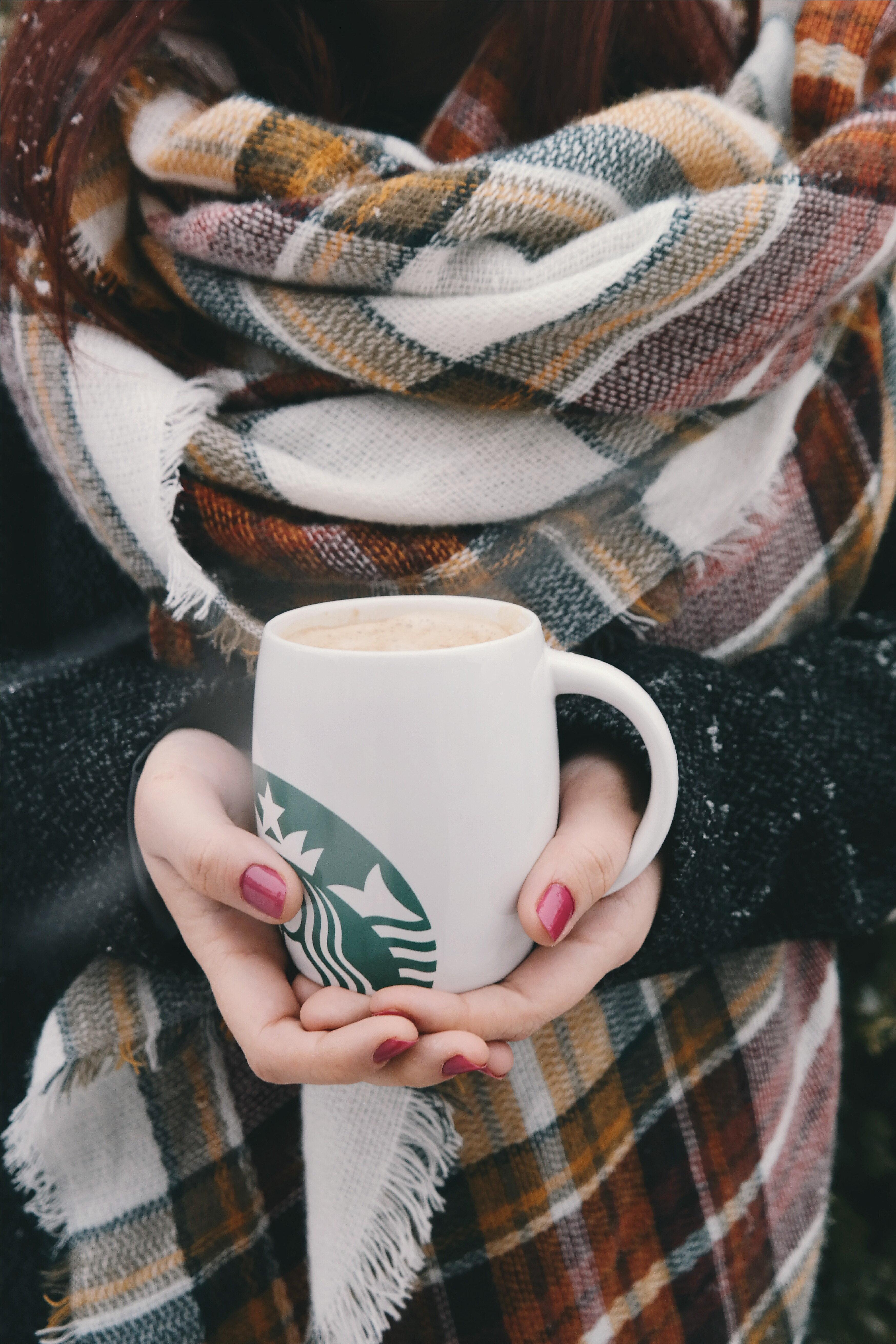 A young woman wearing a plaid scarf holds a Starbucks mug containing a latte (presumably a pumpkin spice latte).