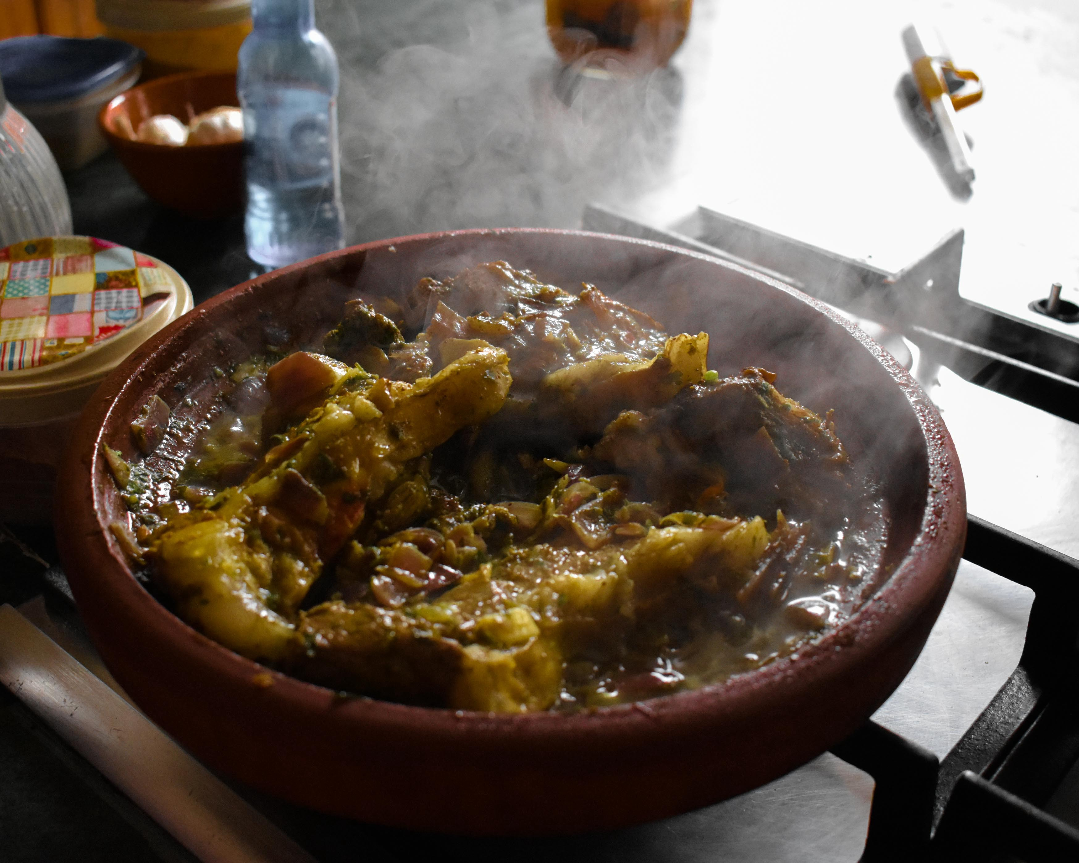 Cooking Tagine or Tajine in Marrakech, Morocco — Lamb Tagine, lamb stew, Moroccan lamb stew in clay pot over stove