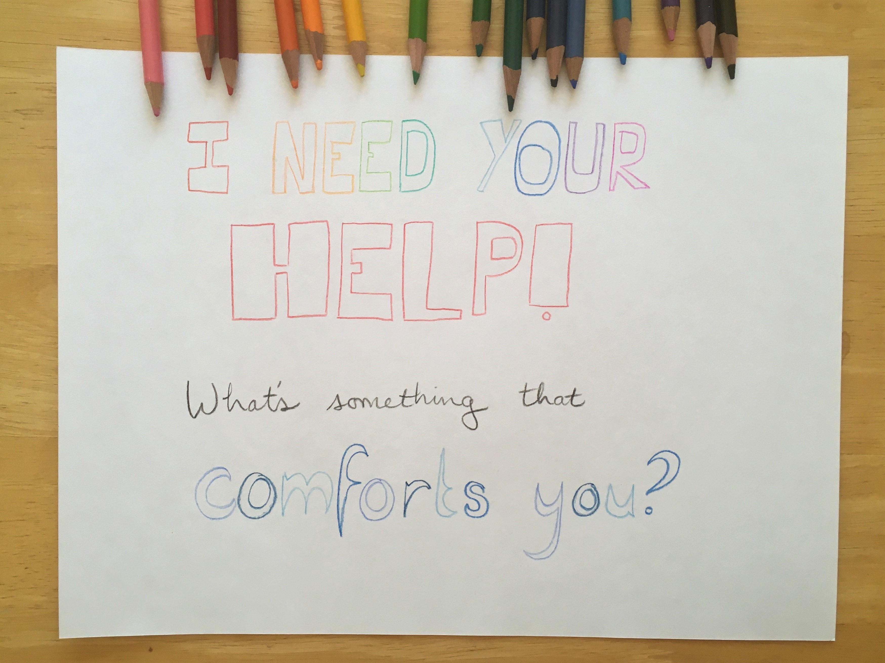 """A simple sheet of white paper with block letters in colored pencil: """"I NEED YOUR HELP! What's something that comforts you?"""""""
