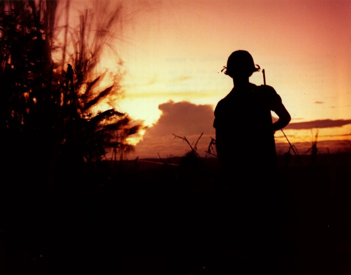 a U.S. soldier looks off into the distance in vietnam. wikimedia commons