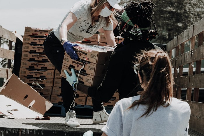 Volunteers move boxes off a truck with their masks on.