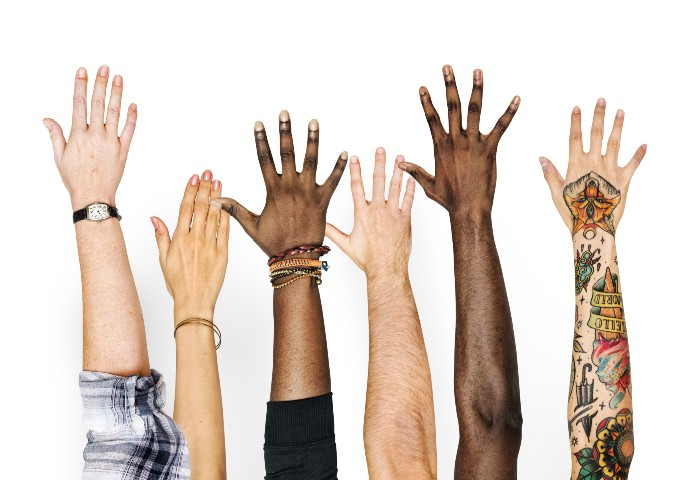 Six hands raised in the air. Physical characteristics indicate they are of different ethnicities, genders and subcultures.