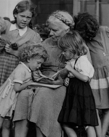 Dorothy Day reading to a group of four young girls.
