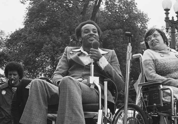 Bradley Lomax and Judith Heumann are both seated in wheelchairs. Bradley was a Black Panther with MS and disability rights activist