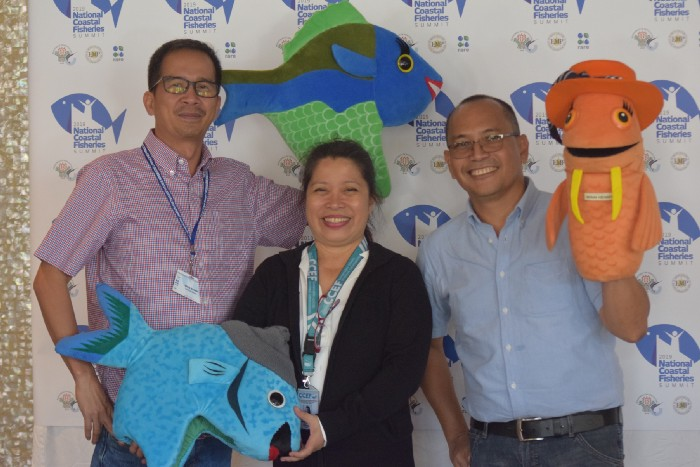 Attendees pose with fish mascot puppets, a popular social marketing tool.