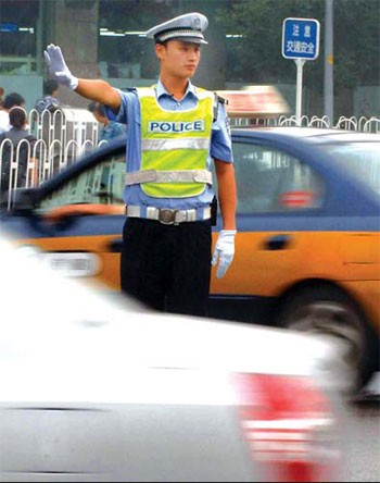 A traffic cop holding out his hand to stop cars.