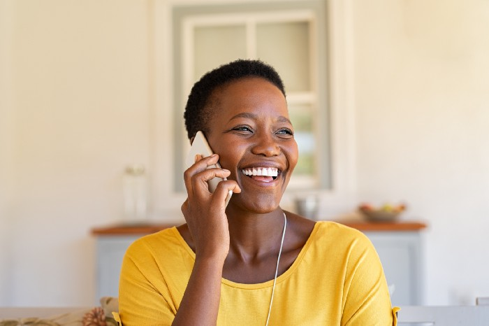 A woman laughing while talking on phone.