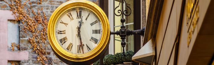 An old clock with Roman numerals, attached to the outside of a shop.