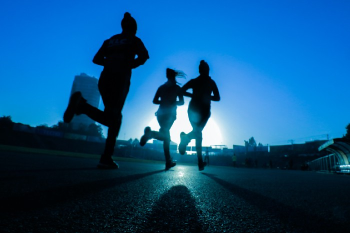 Women running outside early in the morning with shadows around them