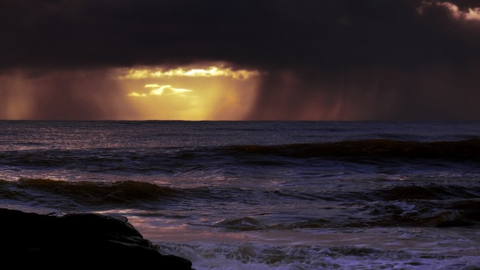Dark raining clouds over swelling water, at the very horizon there's a patch of sunshine, and a glimmer of hope.