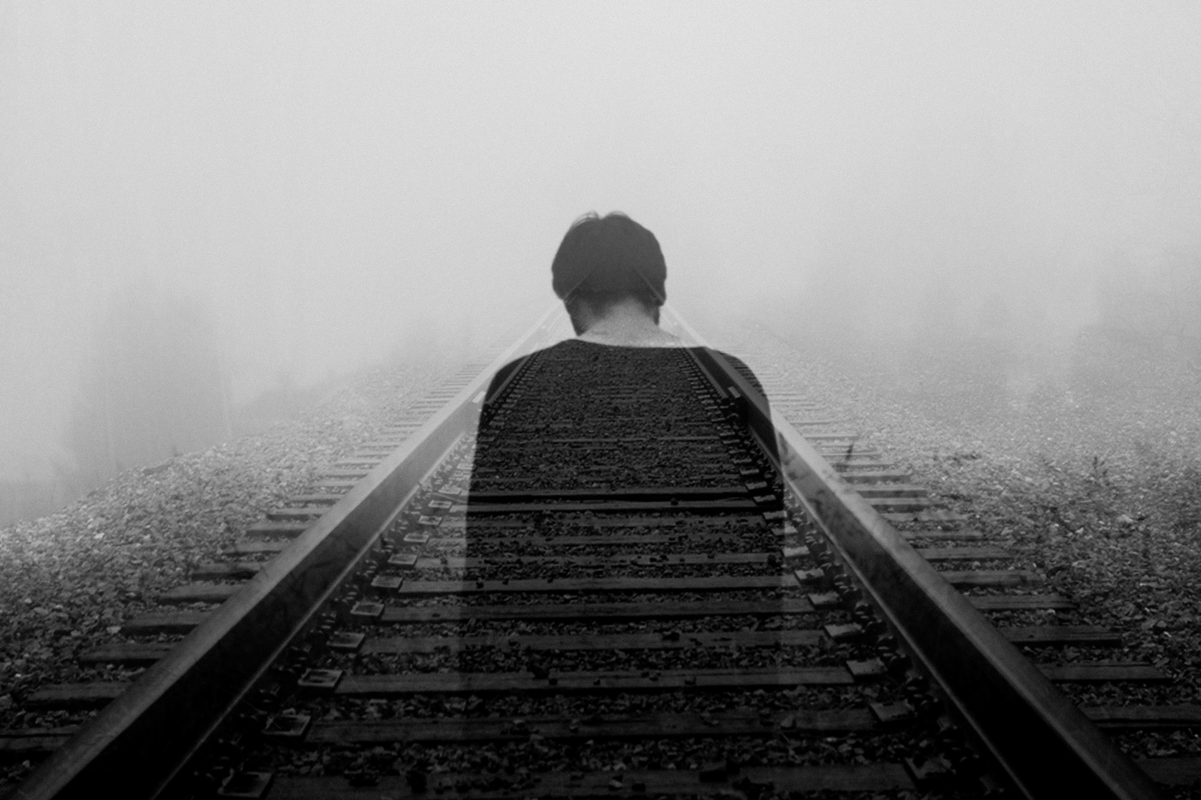 ghostly image of man walking down railroad tracks feeling as if he has lost everything