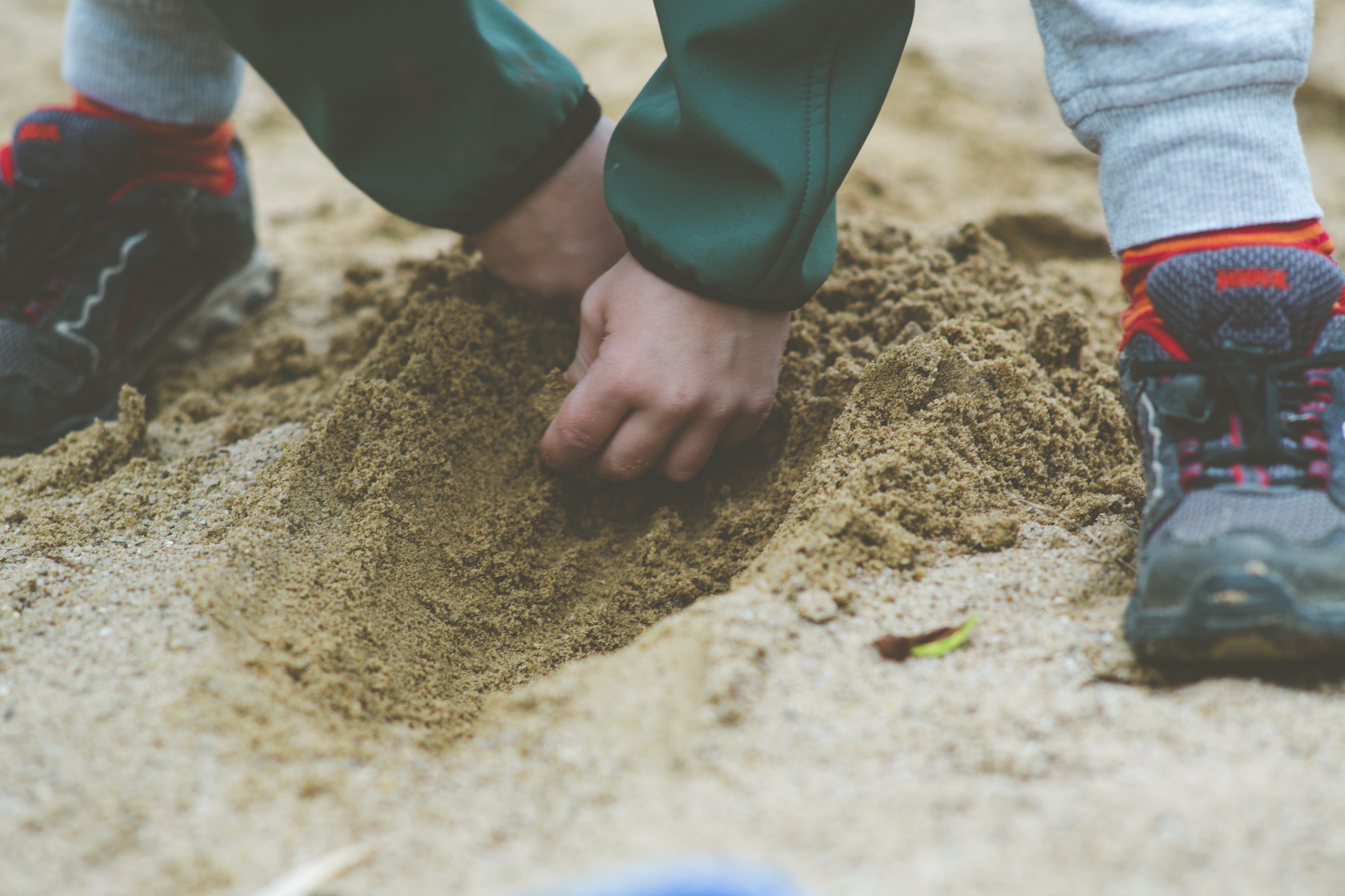 A child digs through sand.