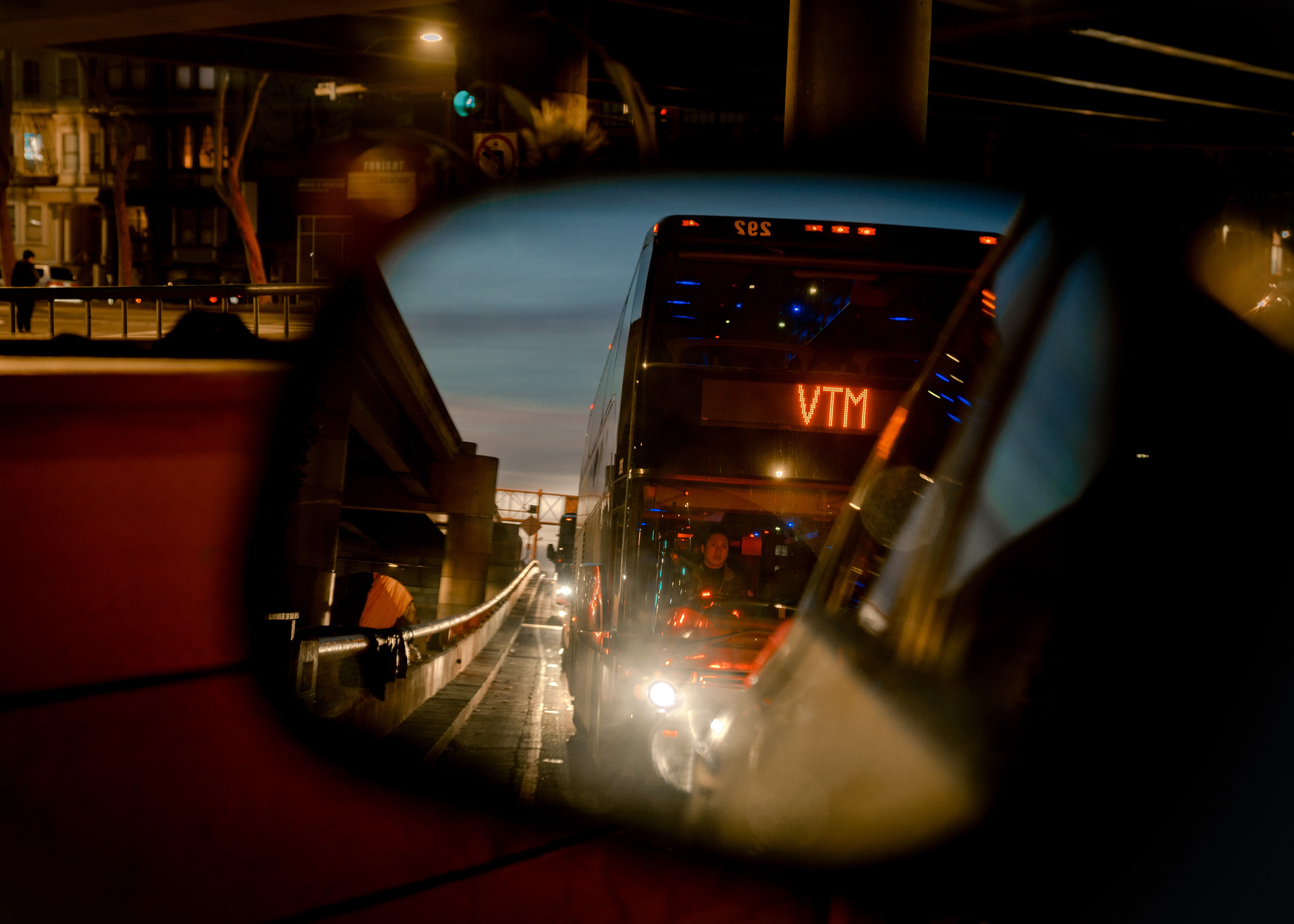 """Reflection of a tech shuttle bus with the text """"MTV"""" (Mountain View) on its front is seen through a car's wing view mirror."""